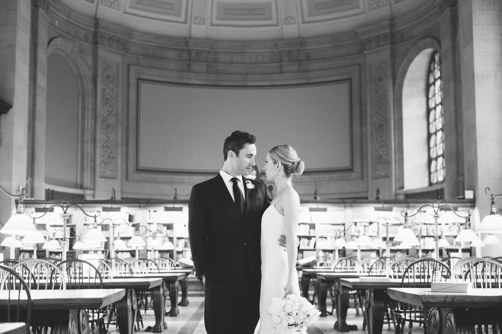 romantic black and white portrait of bride and groom in reading room at Boston Public Library