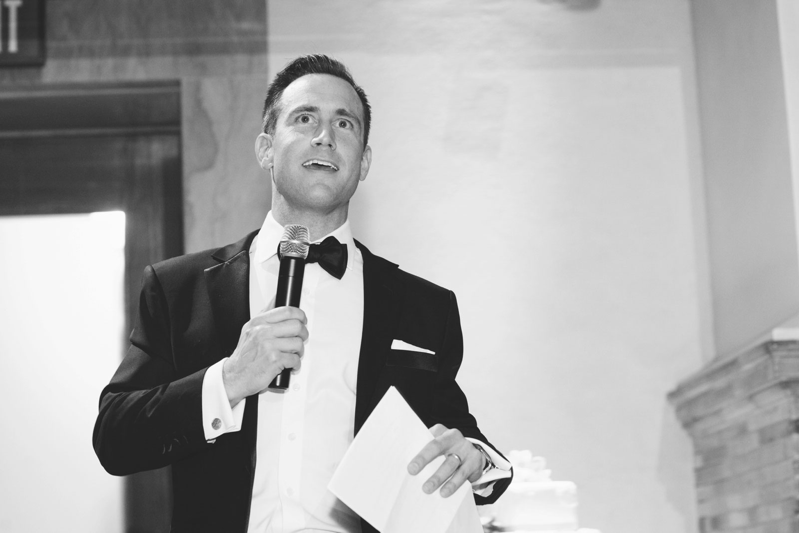 Black and white shot of best man giving speech at his brother's wedding reception at the BPL