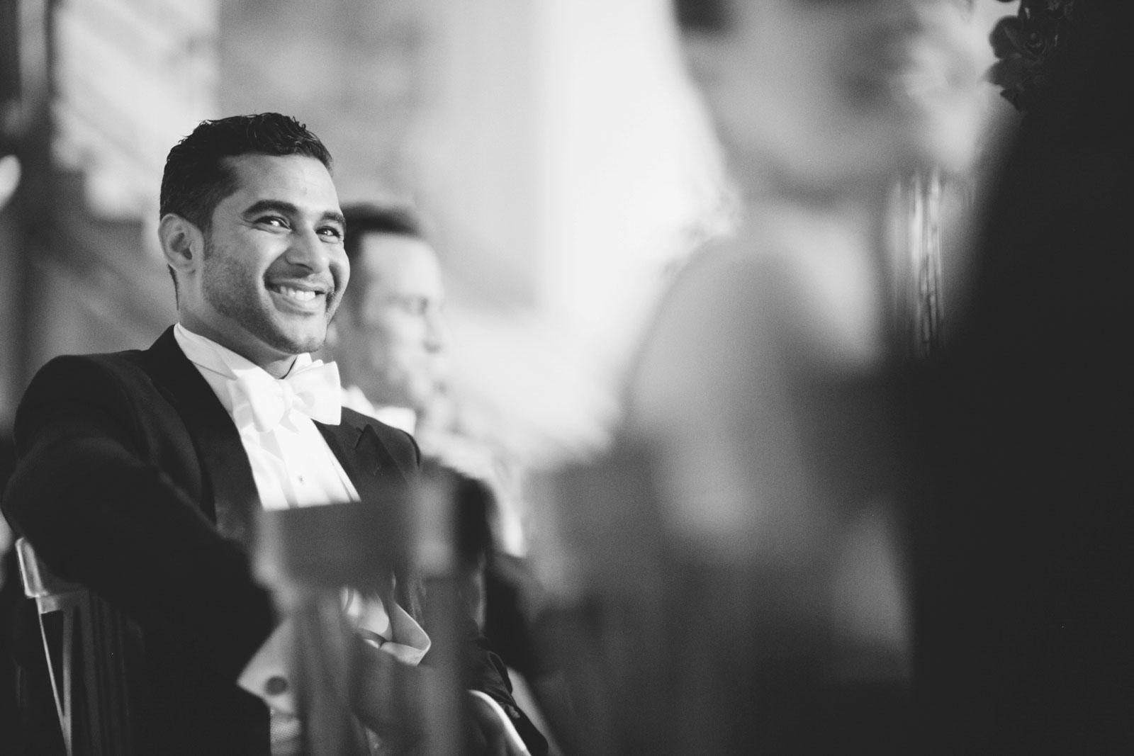 Black and white shot of groom smiling in response to best man speech at his wedding reception