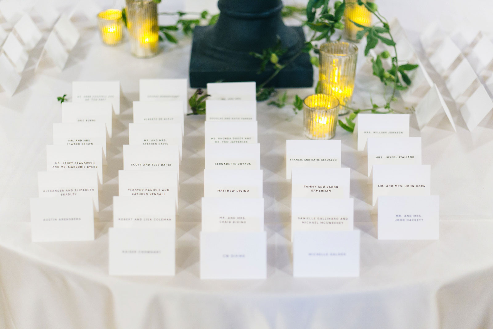 close up shot of simple white place cards, floral centerpeice with lots of greenery and gold candles