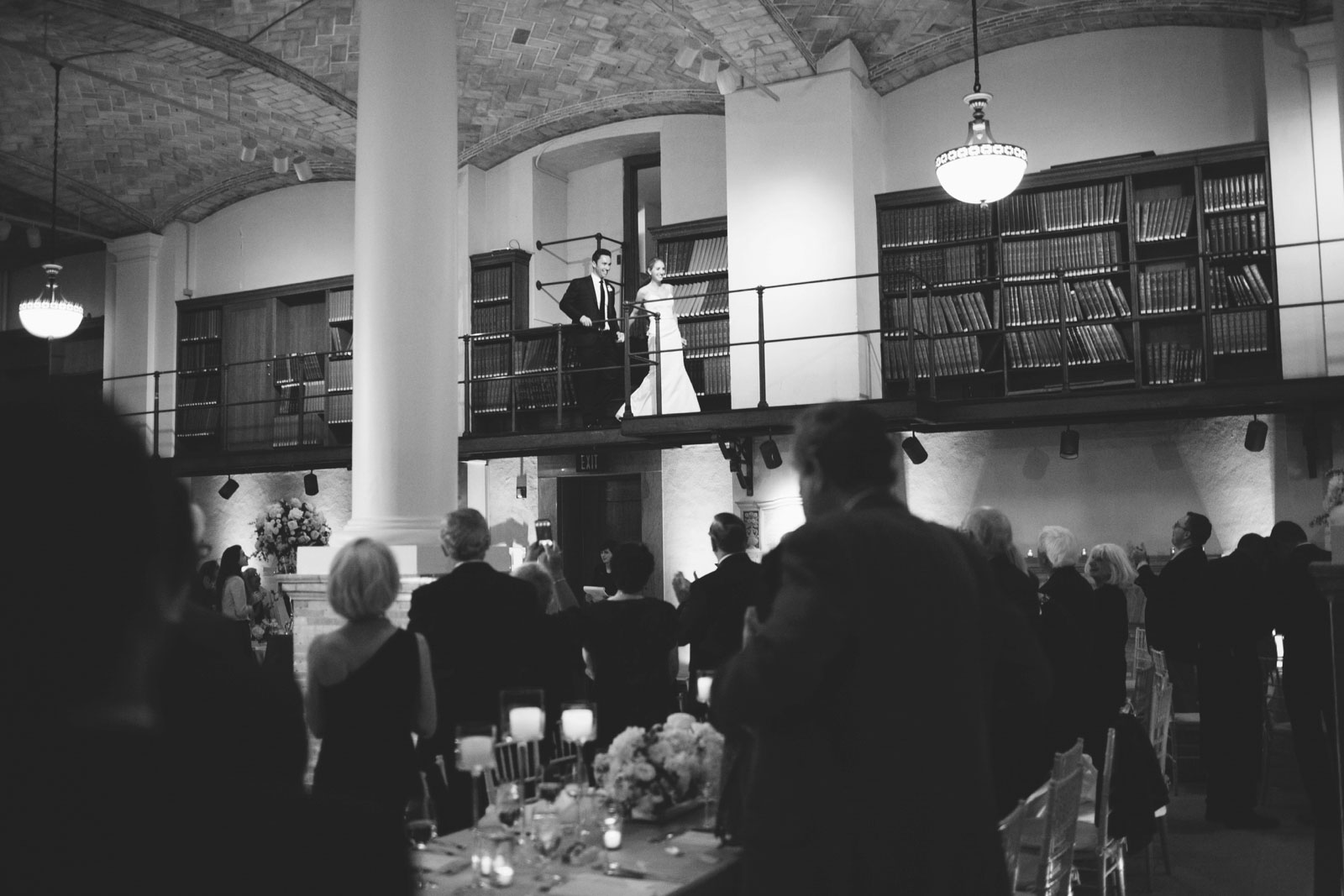 black and white shot of bride and groom entering wedding reception from balcony at BPL