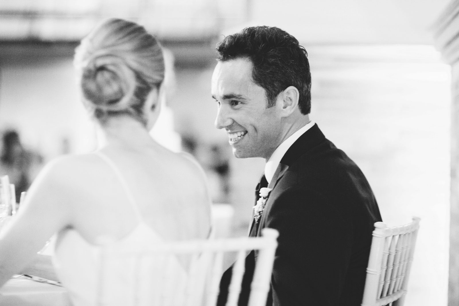 black and white candid of groom laughing during best man speech at romantic BPL wedding