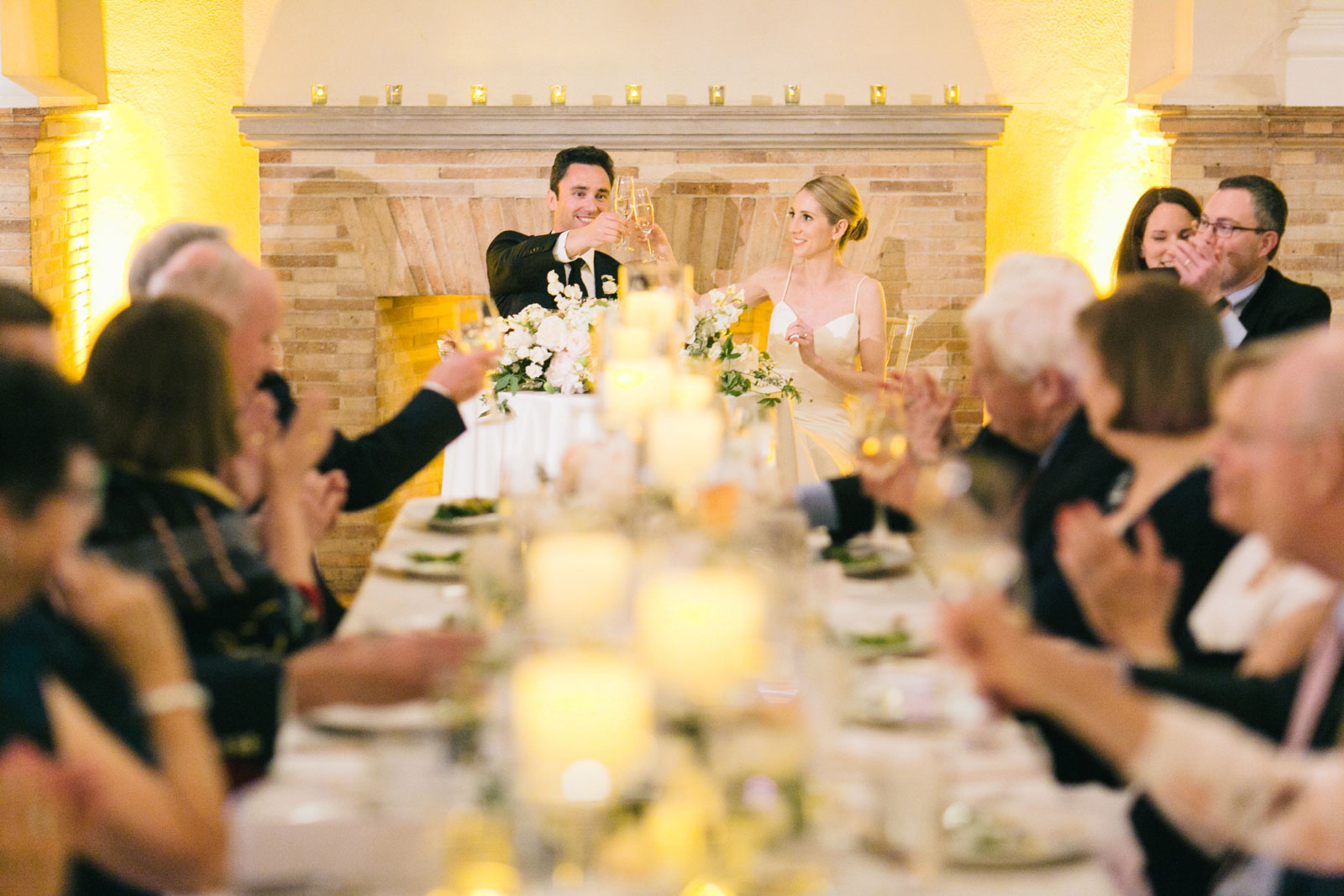bride and groom toast with champagne at their sweetheart table at elegant wedding reception at BPL