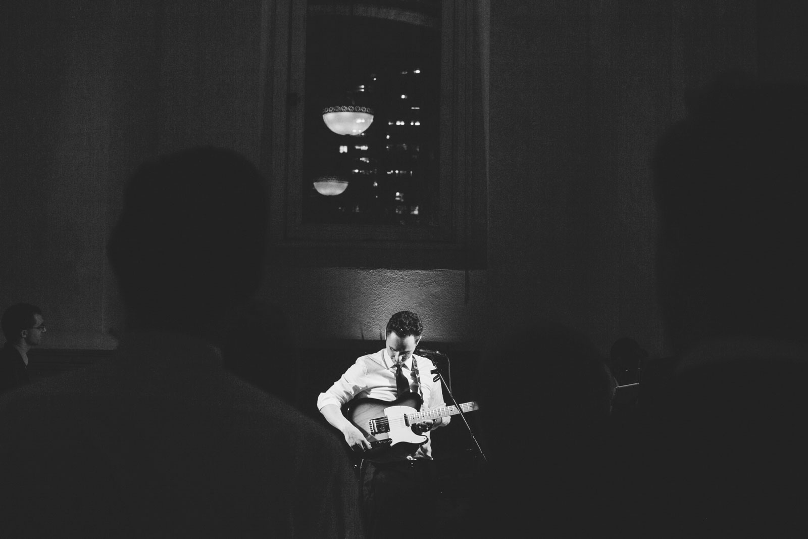 black and white moody shot of groom playing guitar at wedding reception at Boston Public Library