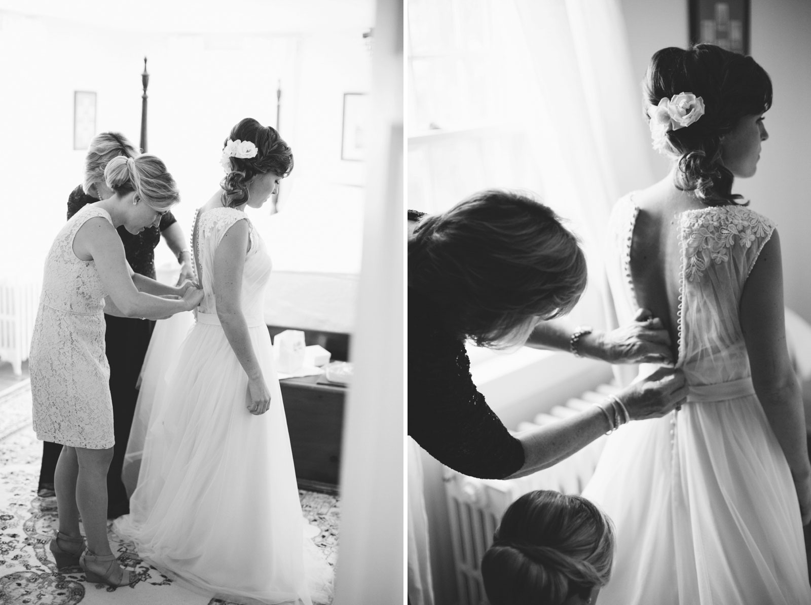 Bridesmaid and mother of the bride help bride into her dress, black and white, natural window light.