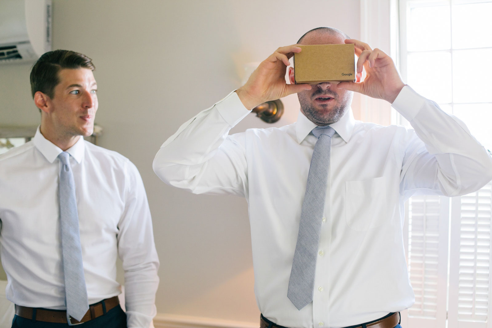 Groomsmen opening their gifts, groomsman playing with google cardboard