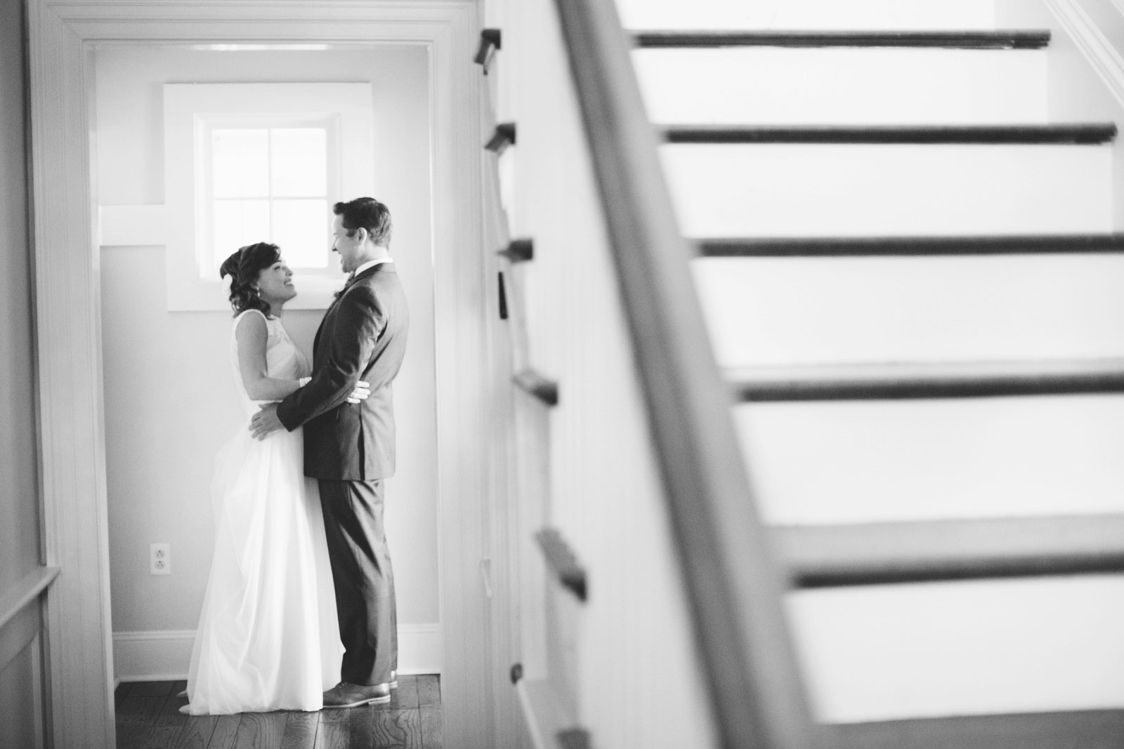bride and groom smiling and talking to each other during first look by staircase, natural light