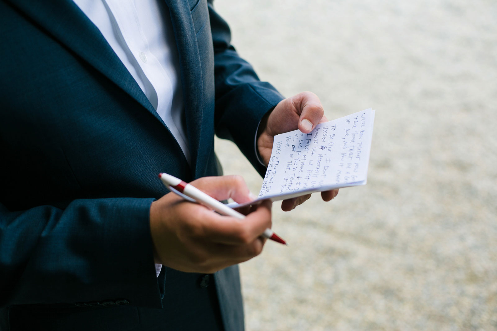 Detail of groom's hand-written vows, groom finishing writing his vows before wedding ceremony.