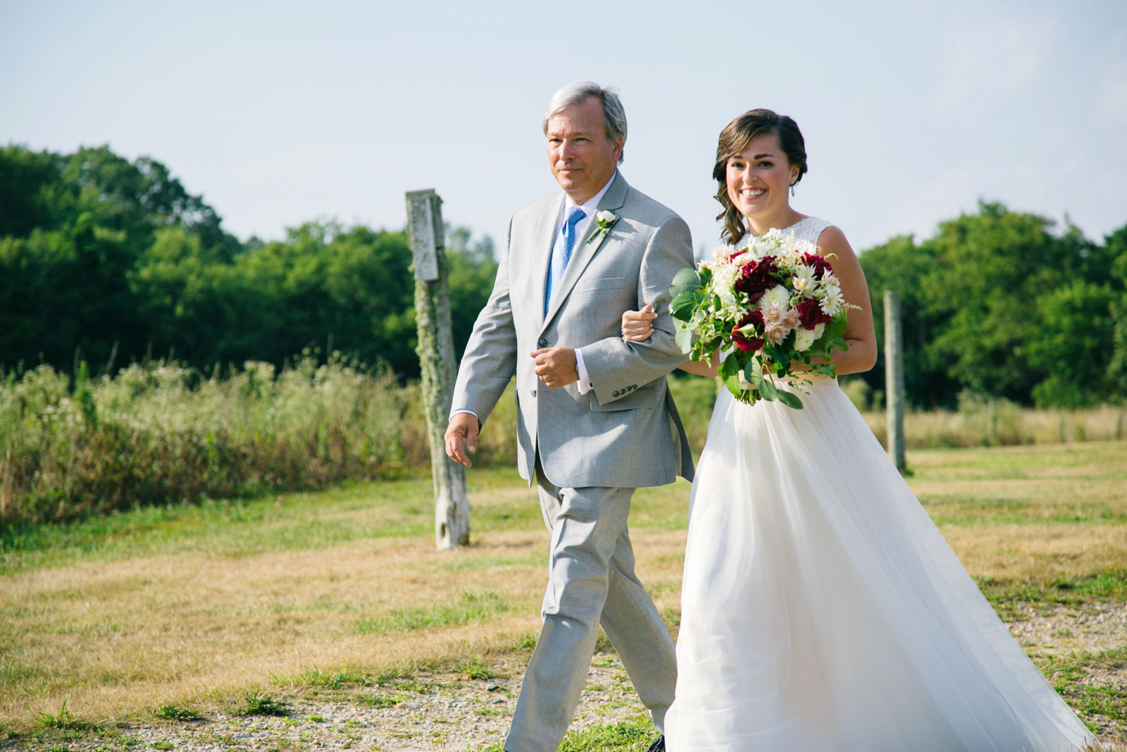 Father of the bride walks bride down the aisle, bride smiling, sunny summer afternoon wedding