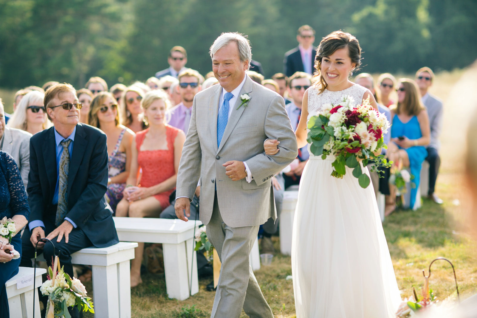 Father of the bride walks bride down the aisle, bride smiling, summer afternoon wedding on cape