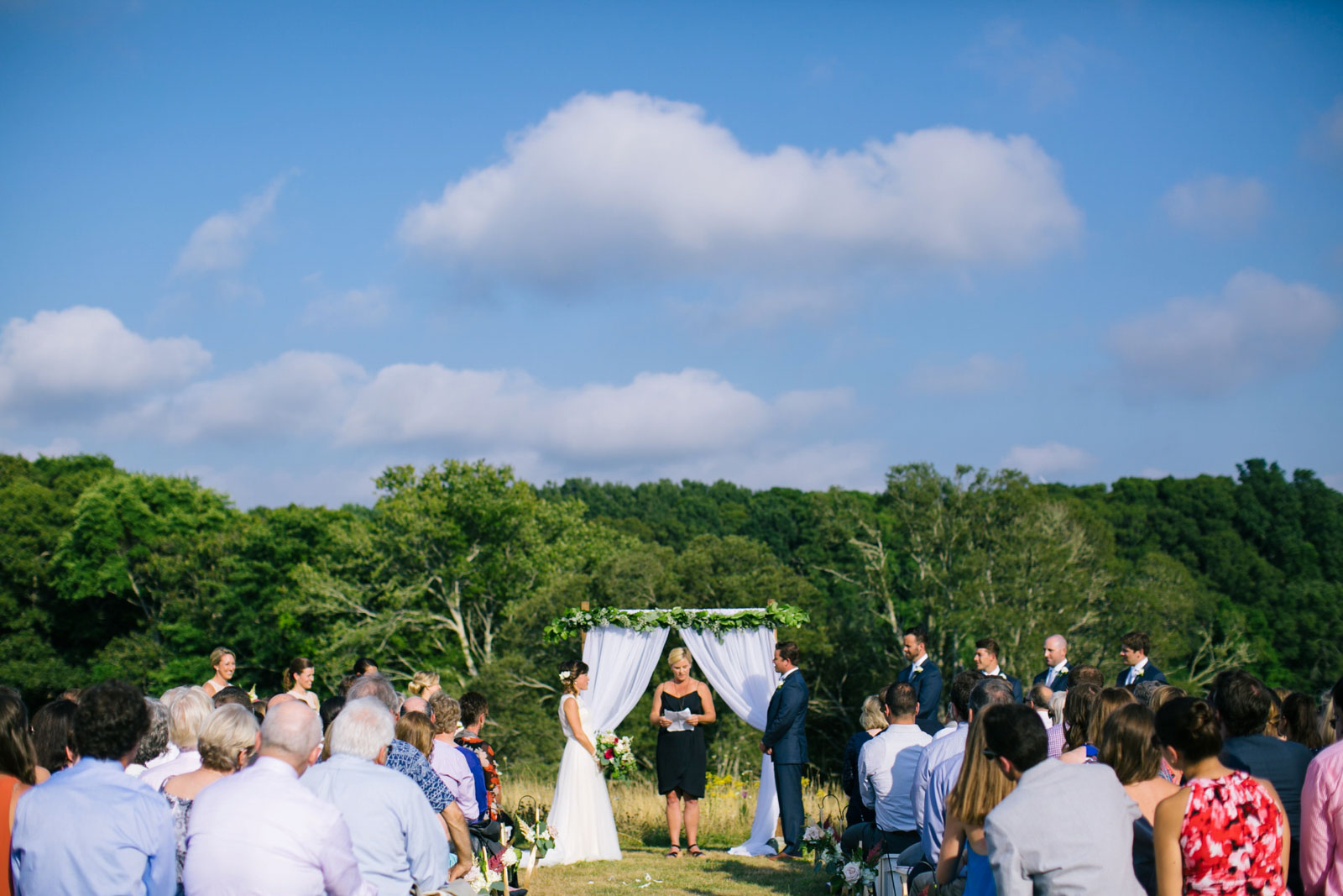Wide shot of wedding ceremony from the back, summer outdoor wedding ceremony on farm