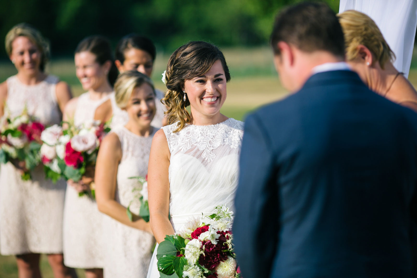 Bride smiling at groom as he says his vows, beautiful natural light, summer wedding on the cape