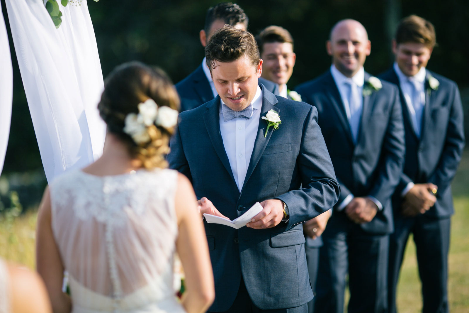 Groom saying his vows, groomsmen smiling in the background, summer outdoor wedding ceremony