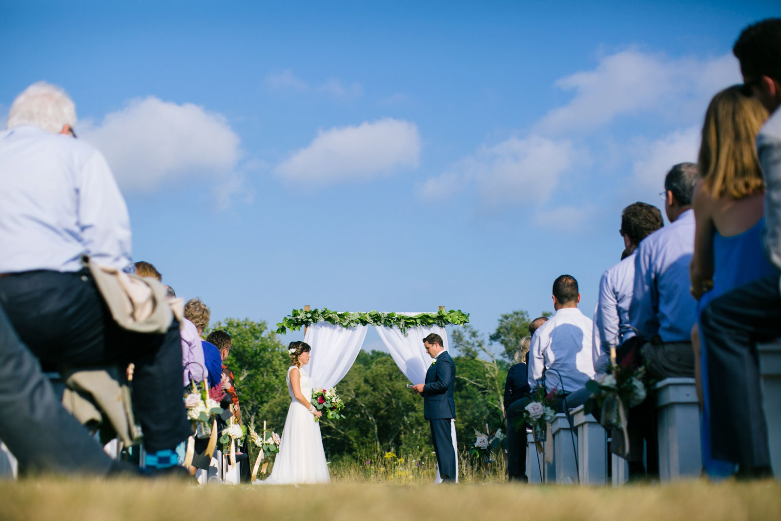 Looking down the aisle from the ground, bride and groom stand under ceremony structure