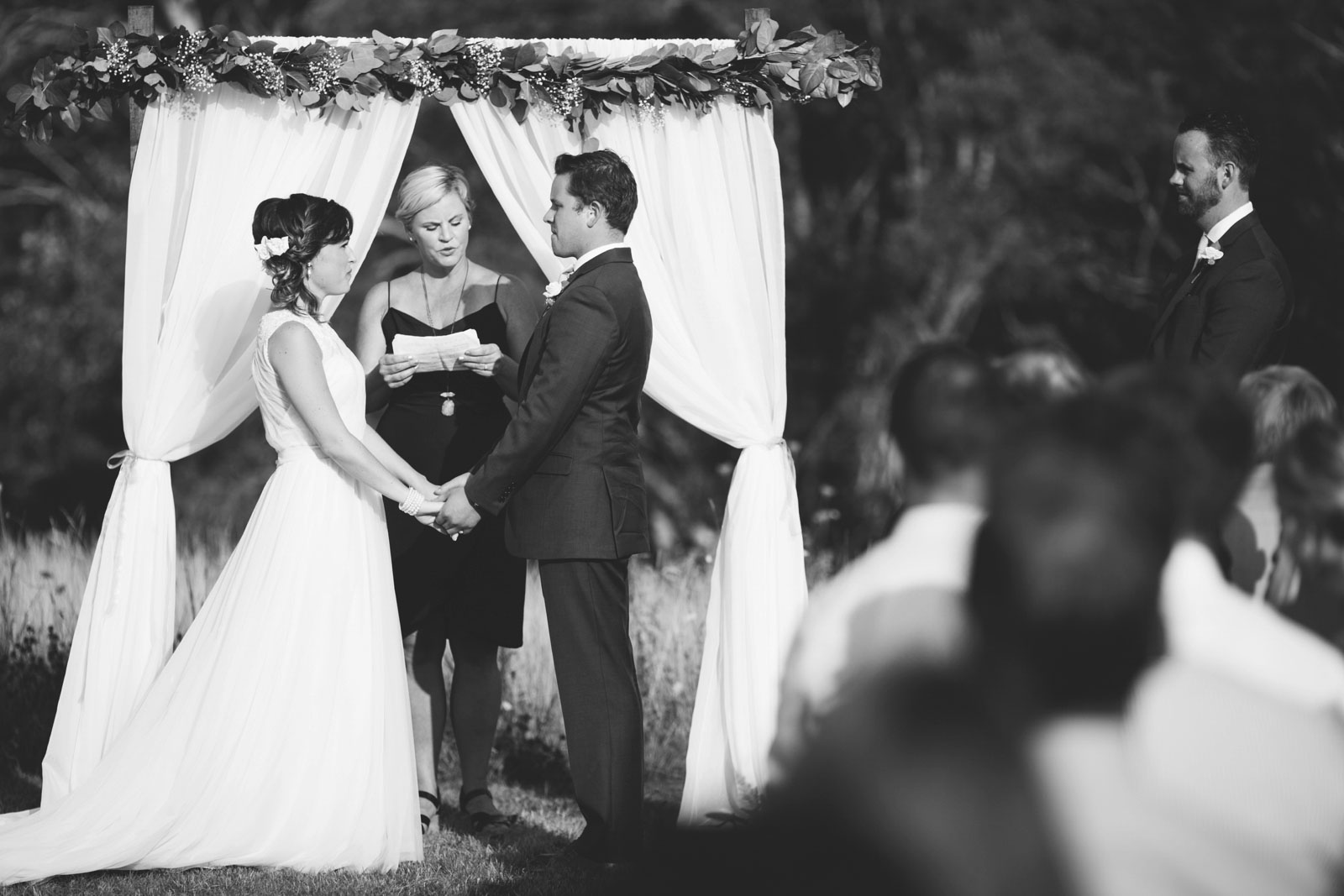 bride and groom hold hands and look into each other's eyes, romantic black and white
