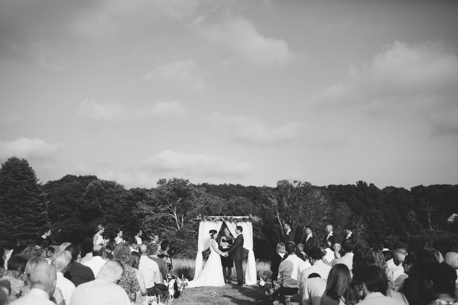 Wide view of wedding ceremony from the back, bride and groom holding hands, black and white