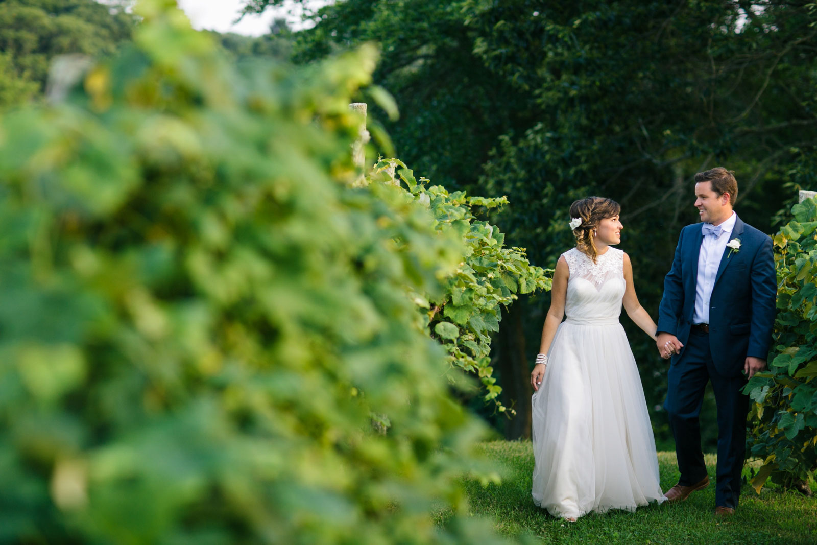 Bride and groom portrait walking through path of grape vines, bride and groom holding hands talking
