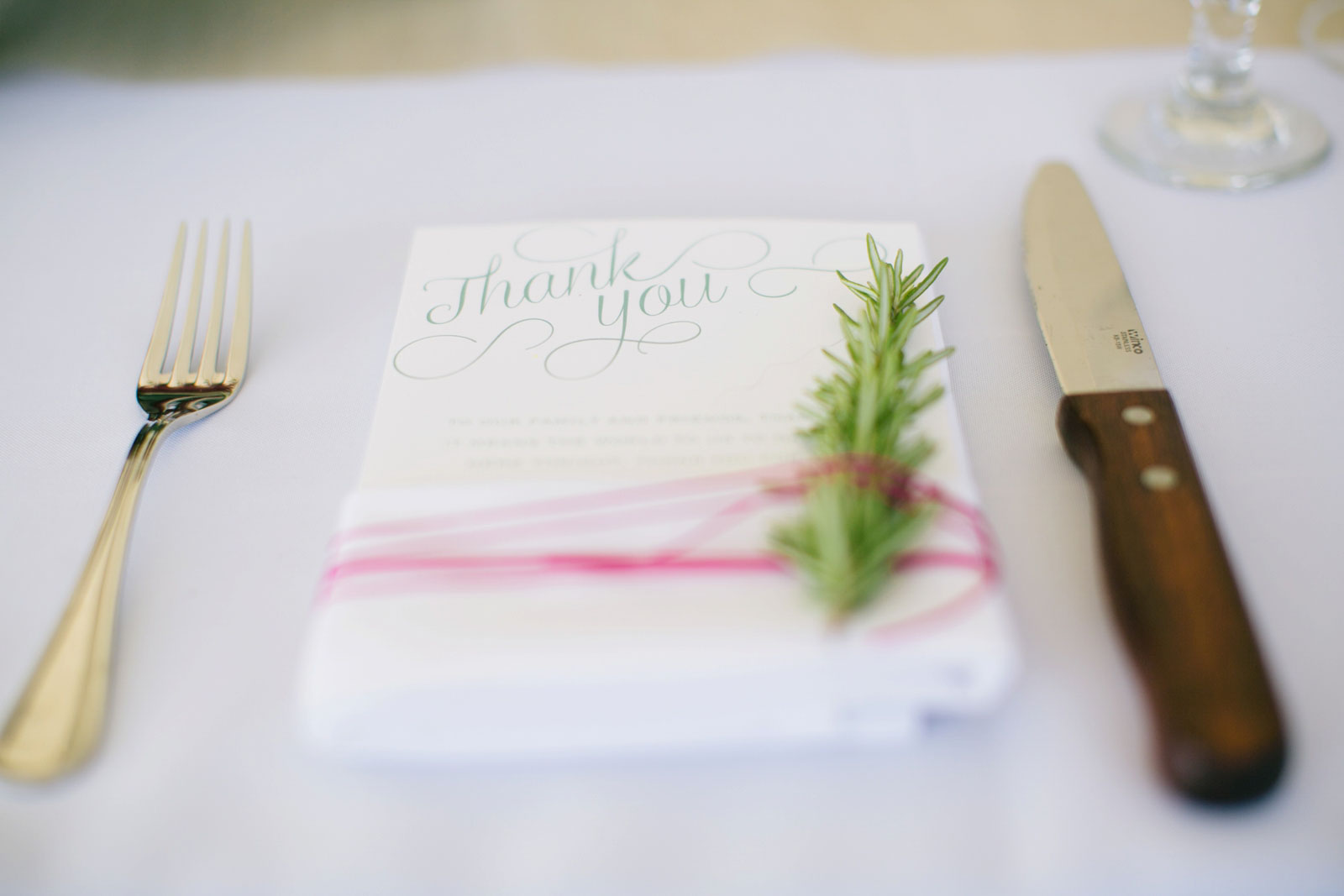 Detail of place setting with thank you note and rosemary sprig tied to menu with pink ribbon.