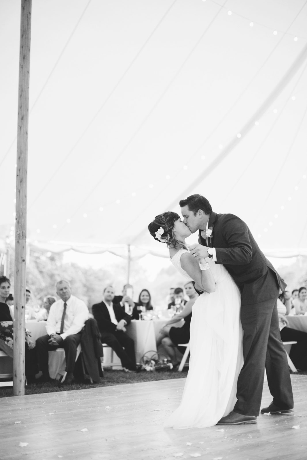 Bride and groom kiss as groom dips bride during first dance, romantic black and white