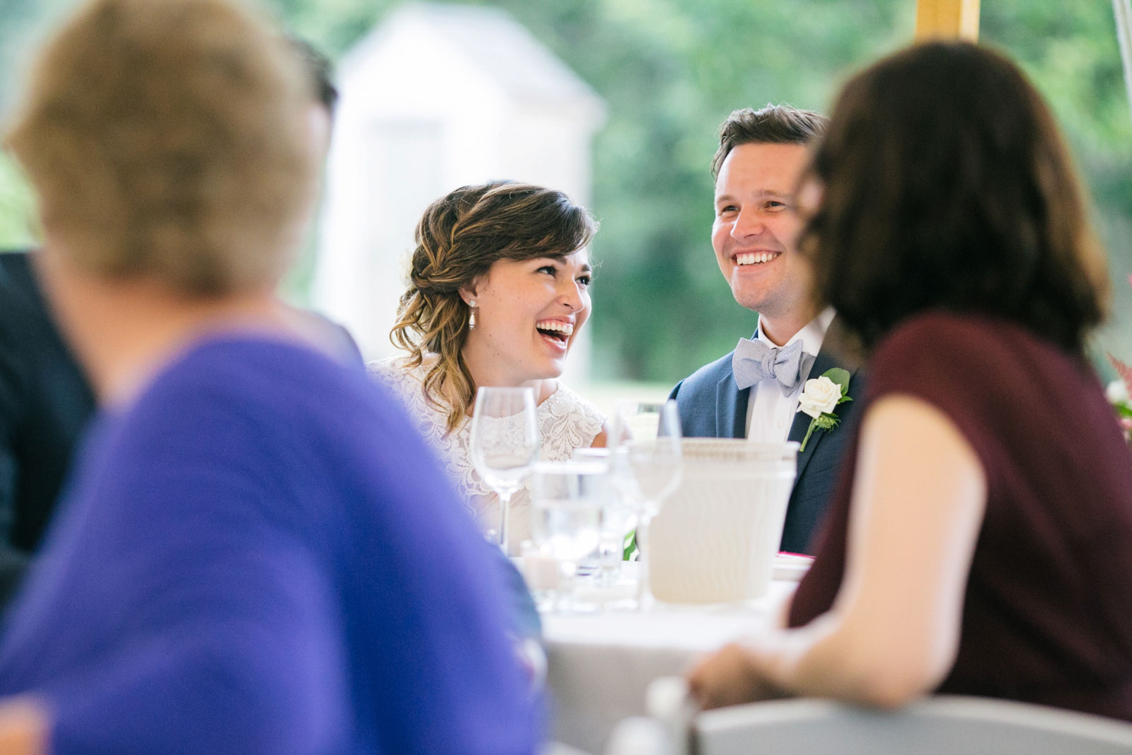 Bride and groom laughing at best man speech, soft natural light at tented summer wedding