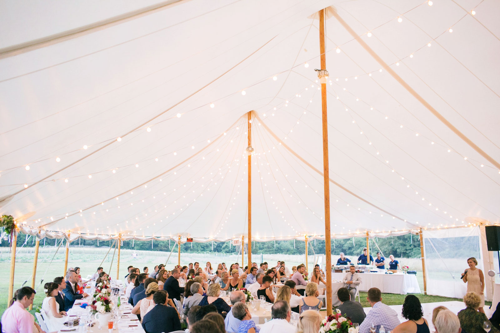 Wide view of wedding reception under tent at summer wedding on Bourne Farm on Cape Cod.