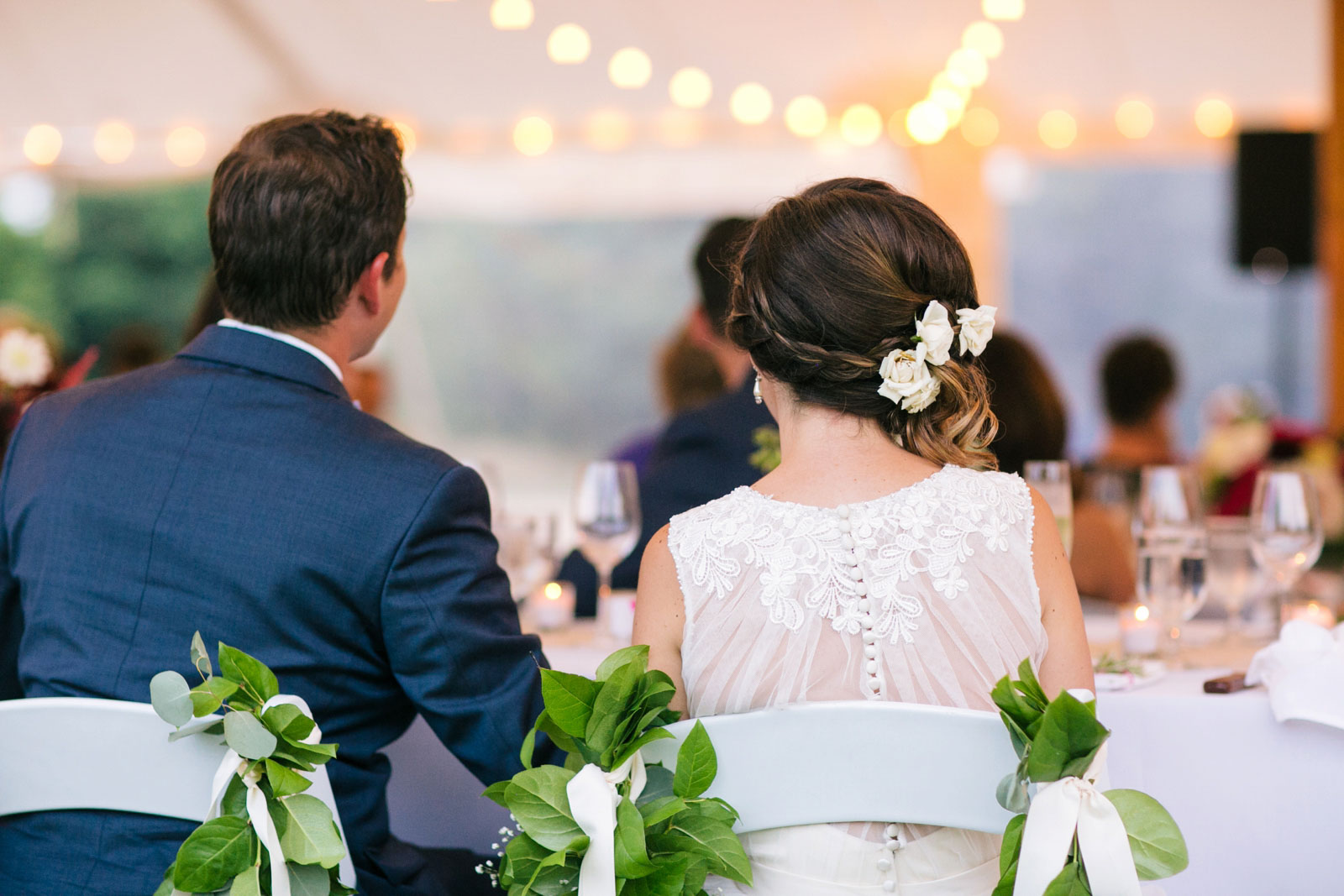 Bride and groom from behind listening to toasts at wedding reception under tent with string lights.