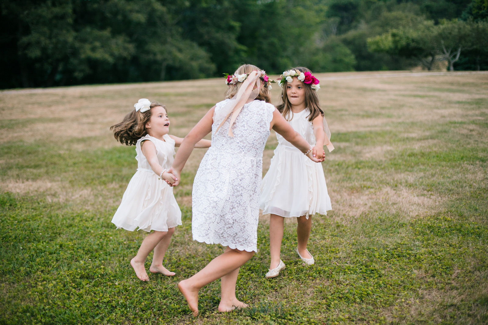Flower girls in white dresses and flower crowns playing on the grass during wedding reception.