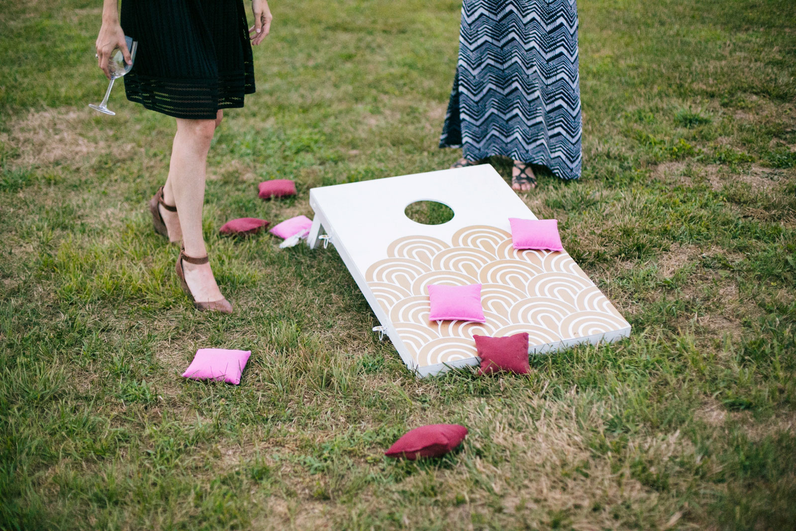 Detail of wedding guests playing cornhole on the grass during outdoor wedding reception.