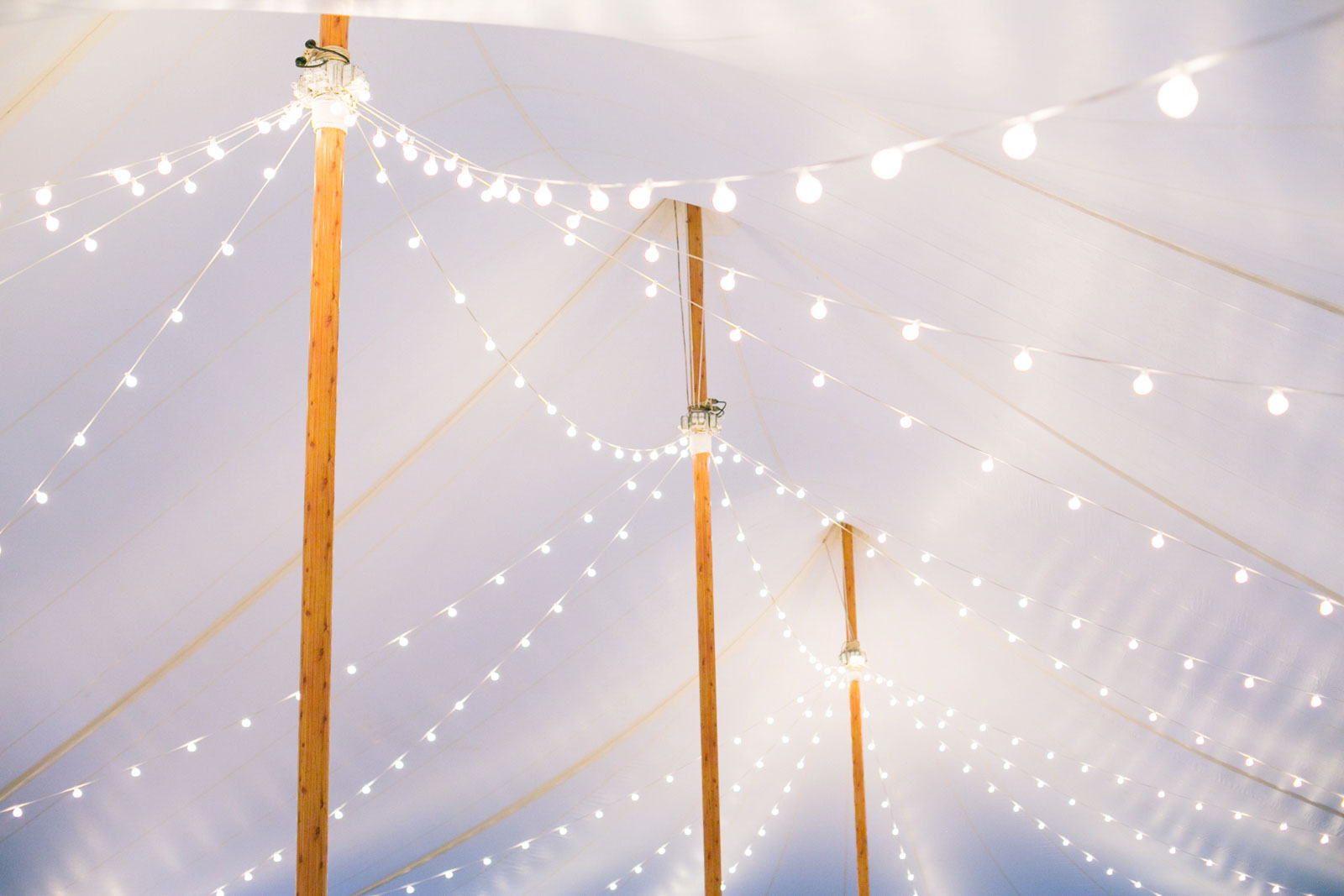 Detail of string lights hanging from poles at tented wedding reception at Bourne Farm on Cape Cod.