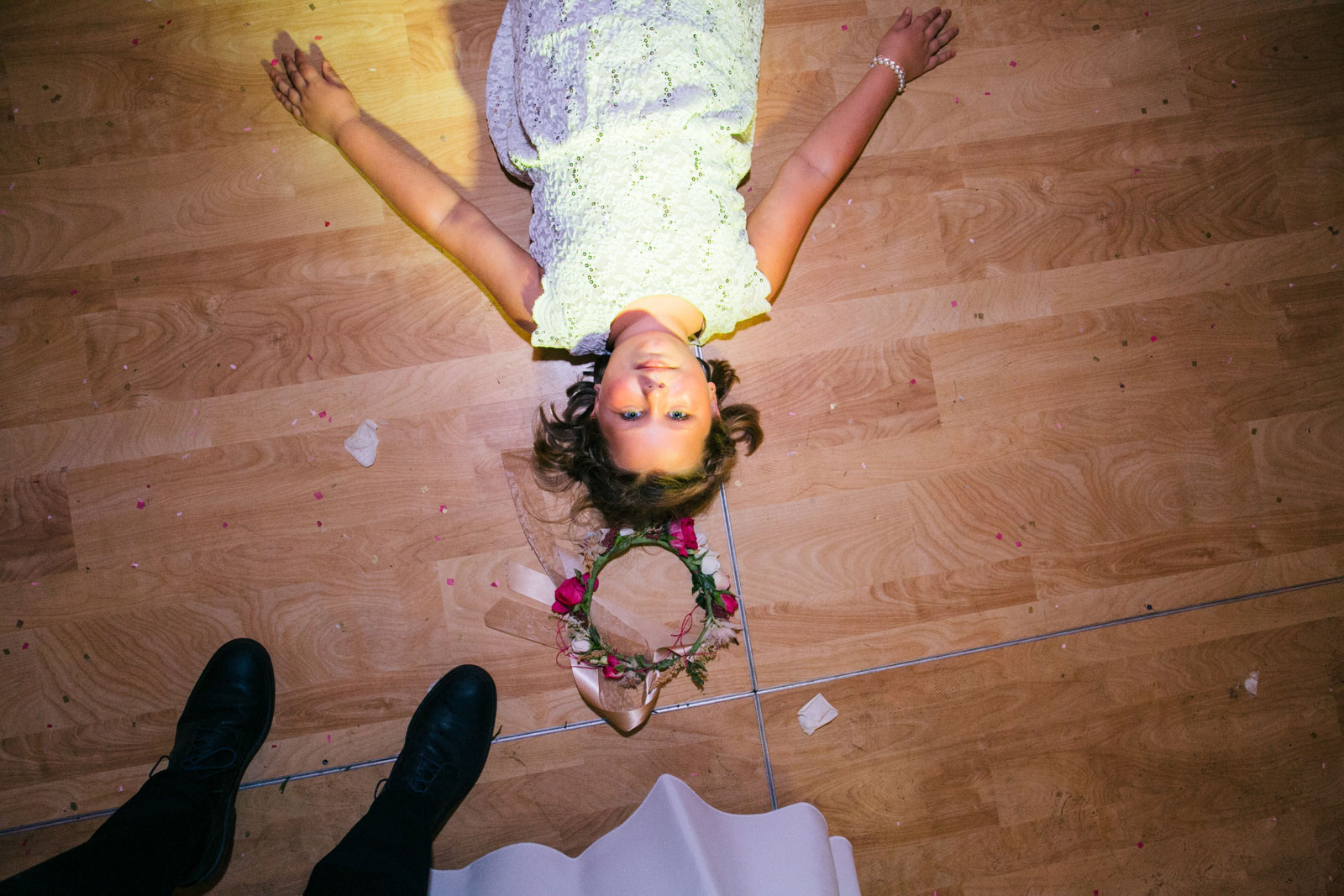 Flower girl being silly laying on the dance floor in front of colored lights from DJ.