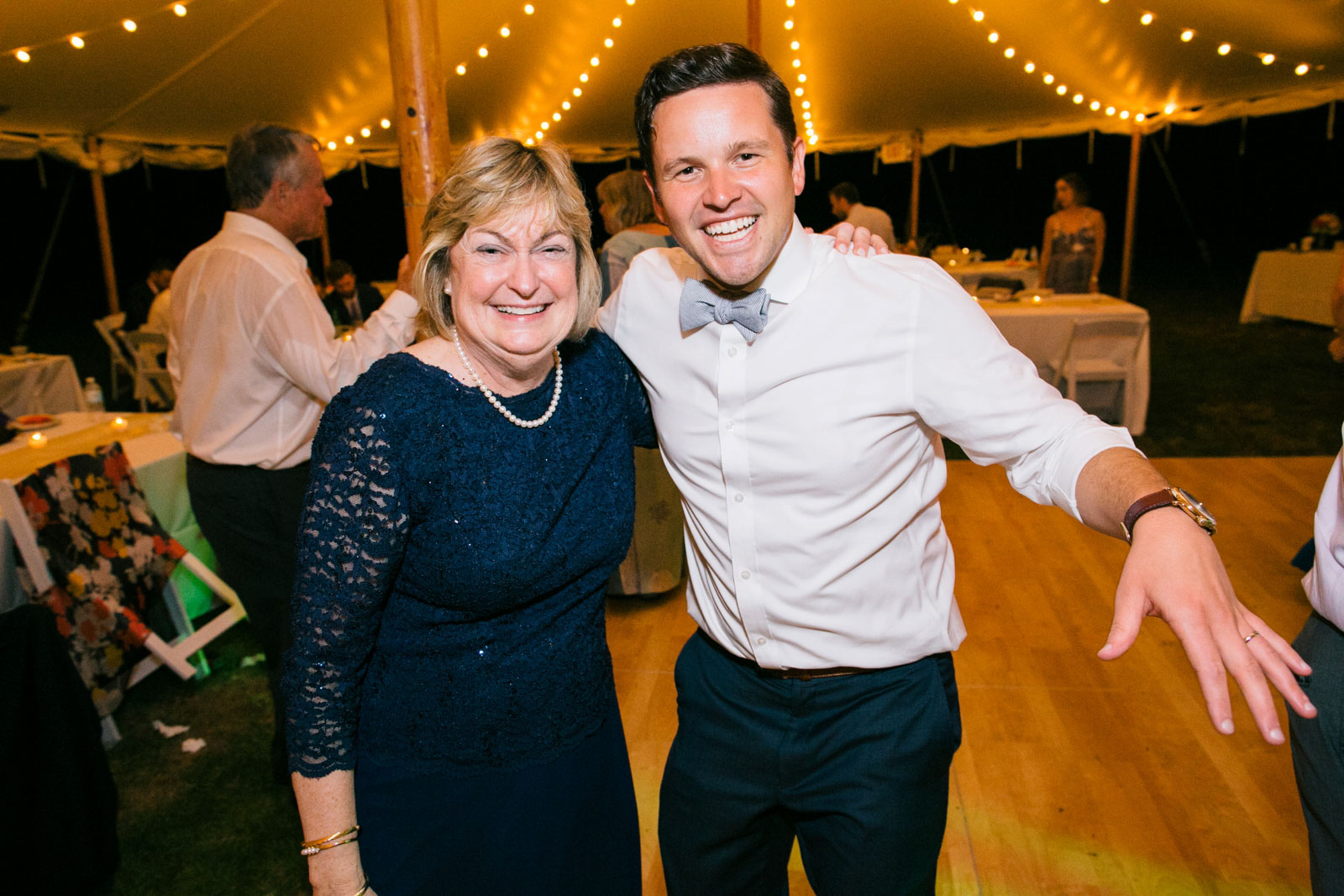 Groom and mother of the bride smiling on the dance floor at tented wedding reception.