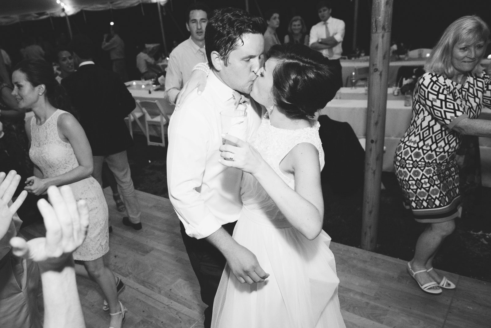 Bride and groom dancing and kissing on the dance floor, romantic black and white.
