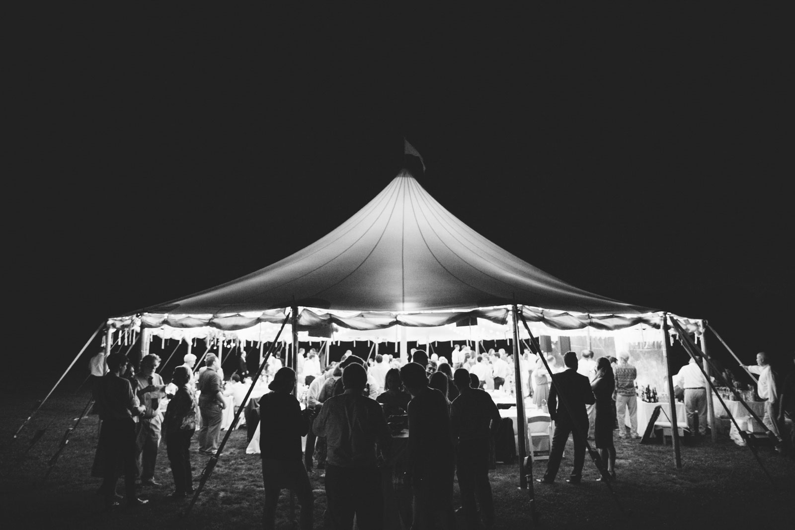 Black and white wide view of tent glowing at the end of the night on Bourne Farm.