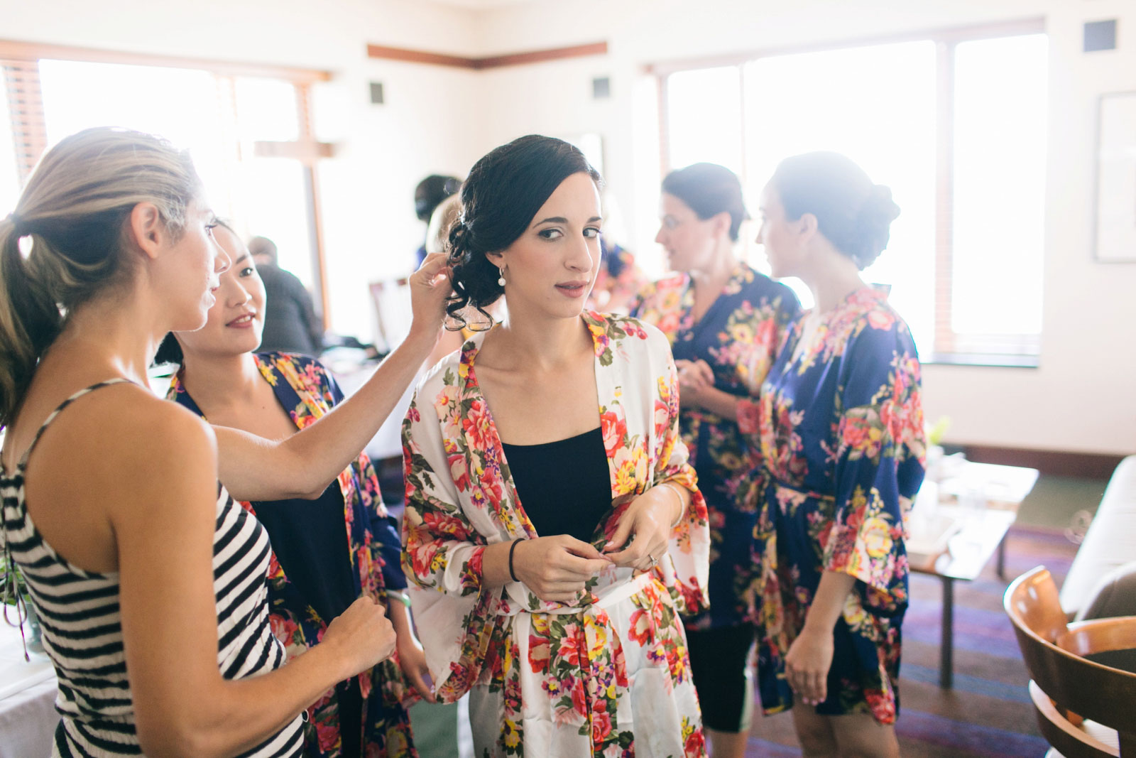 bridesmaids checking out bride's hair in bridal suite with matching silk floral robes