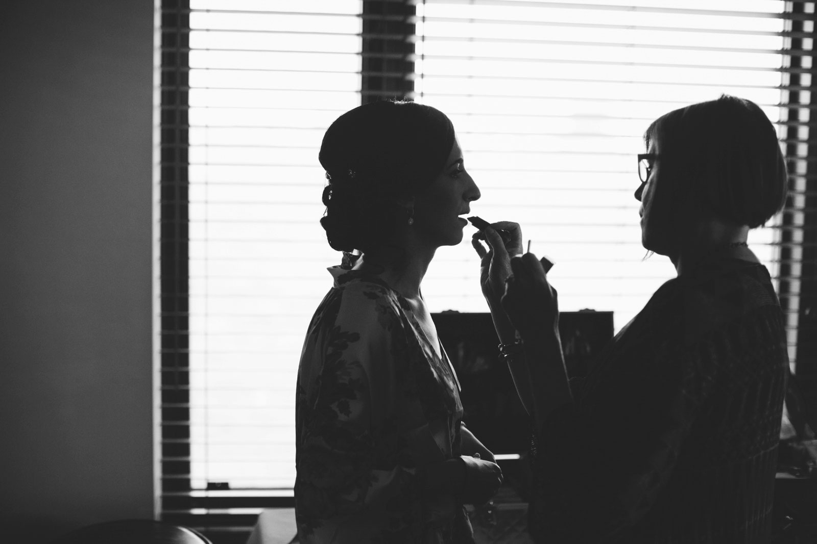 black and white silhouette of bride getting makeup done in front of window in bridal suite at BECC