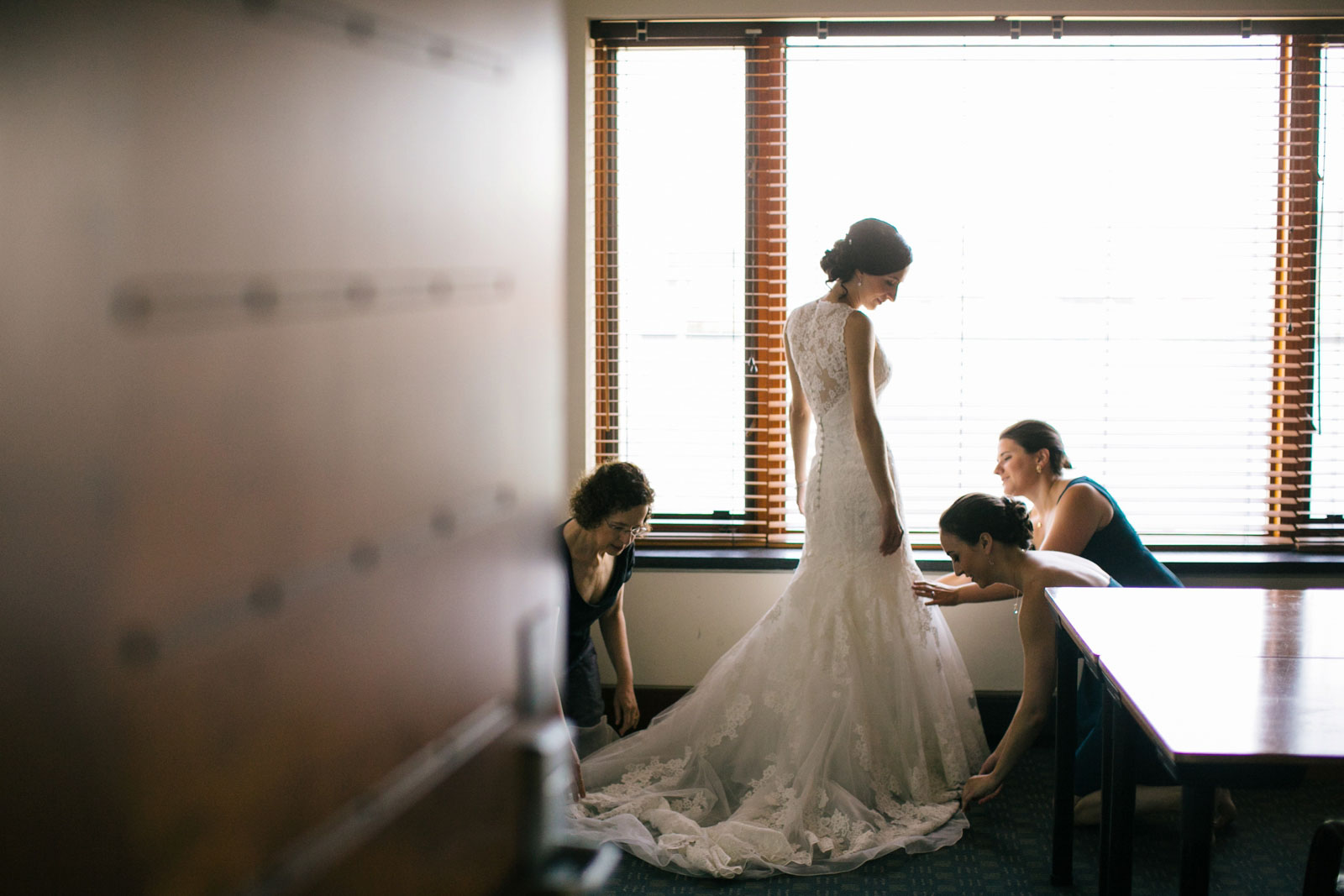 bridesmaids and mother of the bride helping bride into wedding dress in bridal suite at BEC