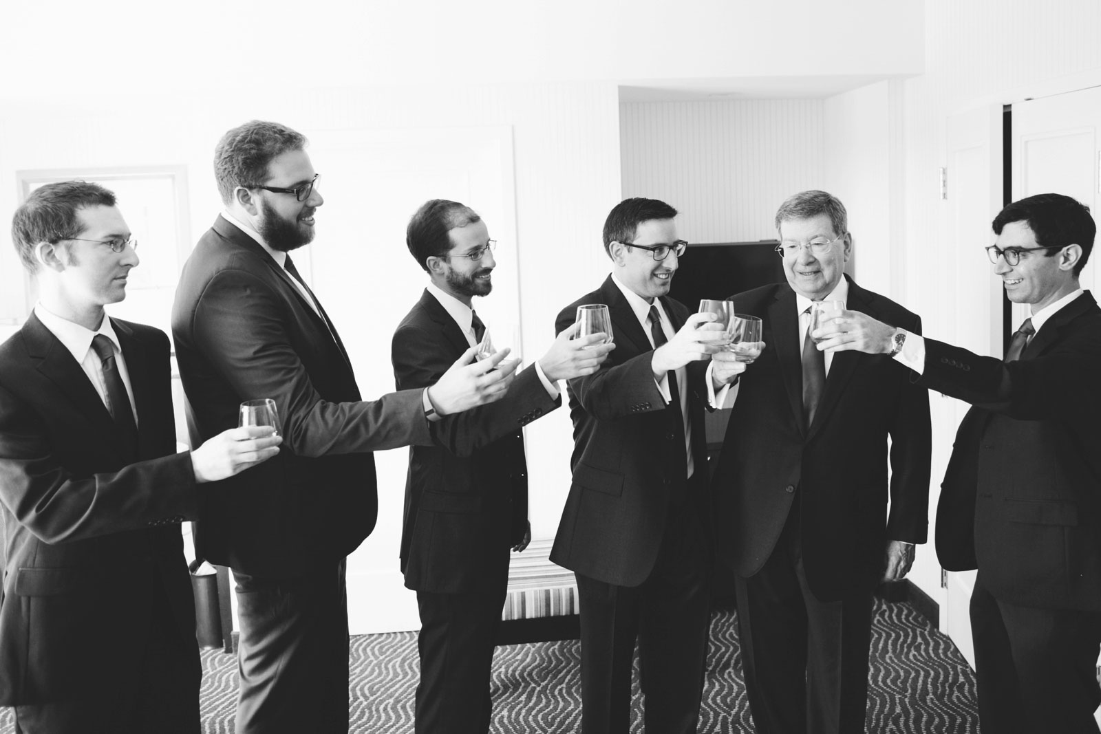 black and white candid of groomsmen sharing a toast while getting ready at Renaissance hotel
