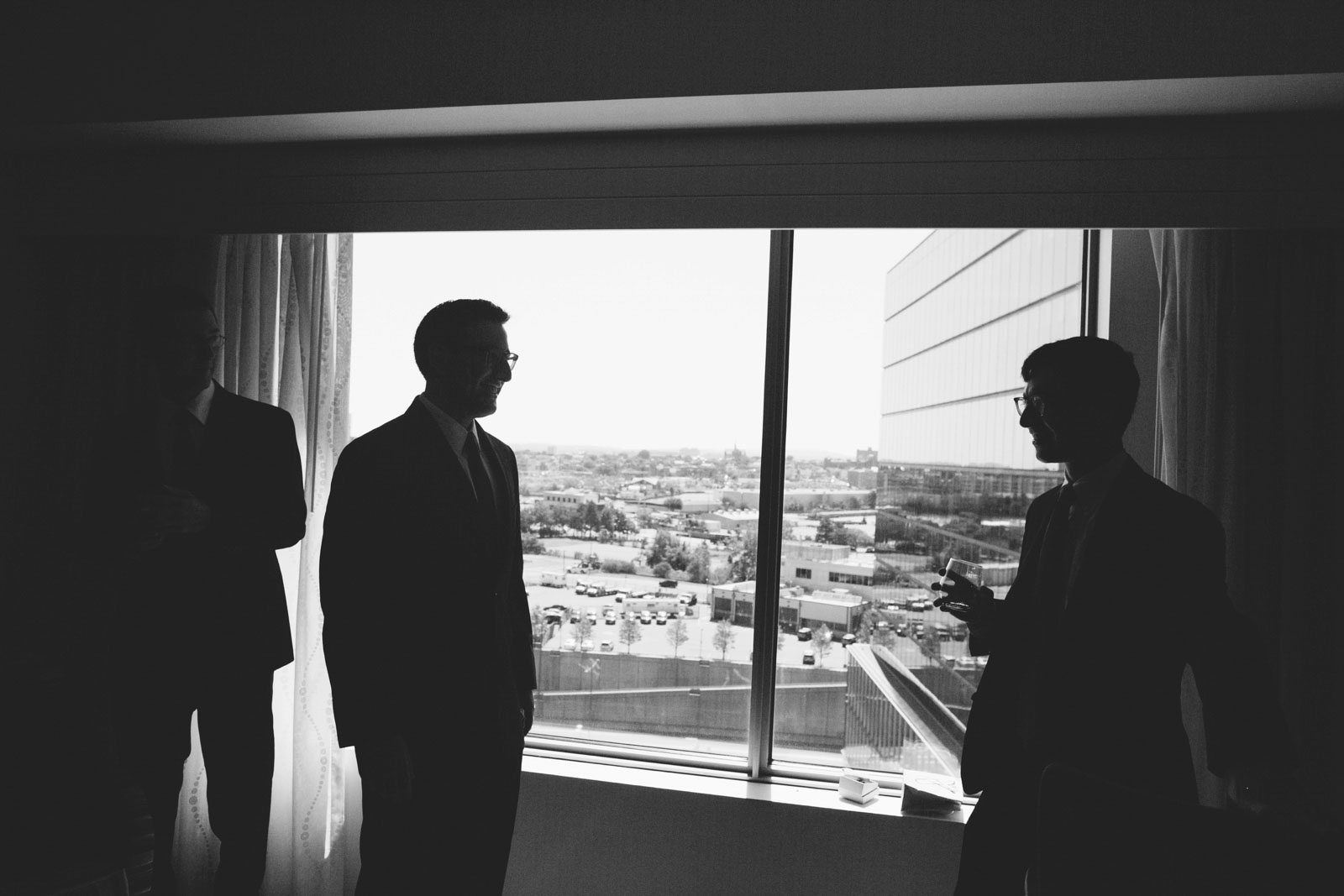 black and white candid silhouette of groomsmen standing in front of window in getting ready suite