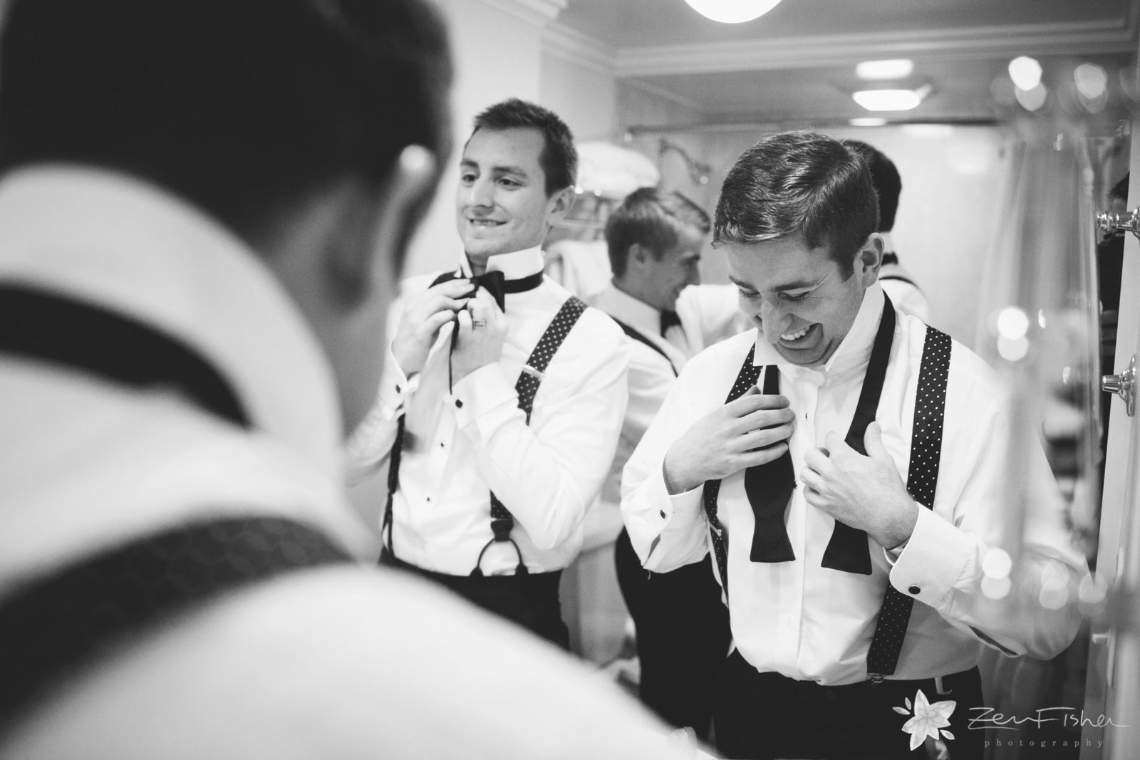 Groom and groomsmen getting ready tying their bowties in the mirror at the hotel room.