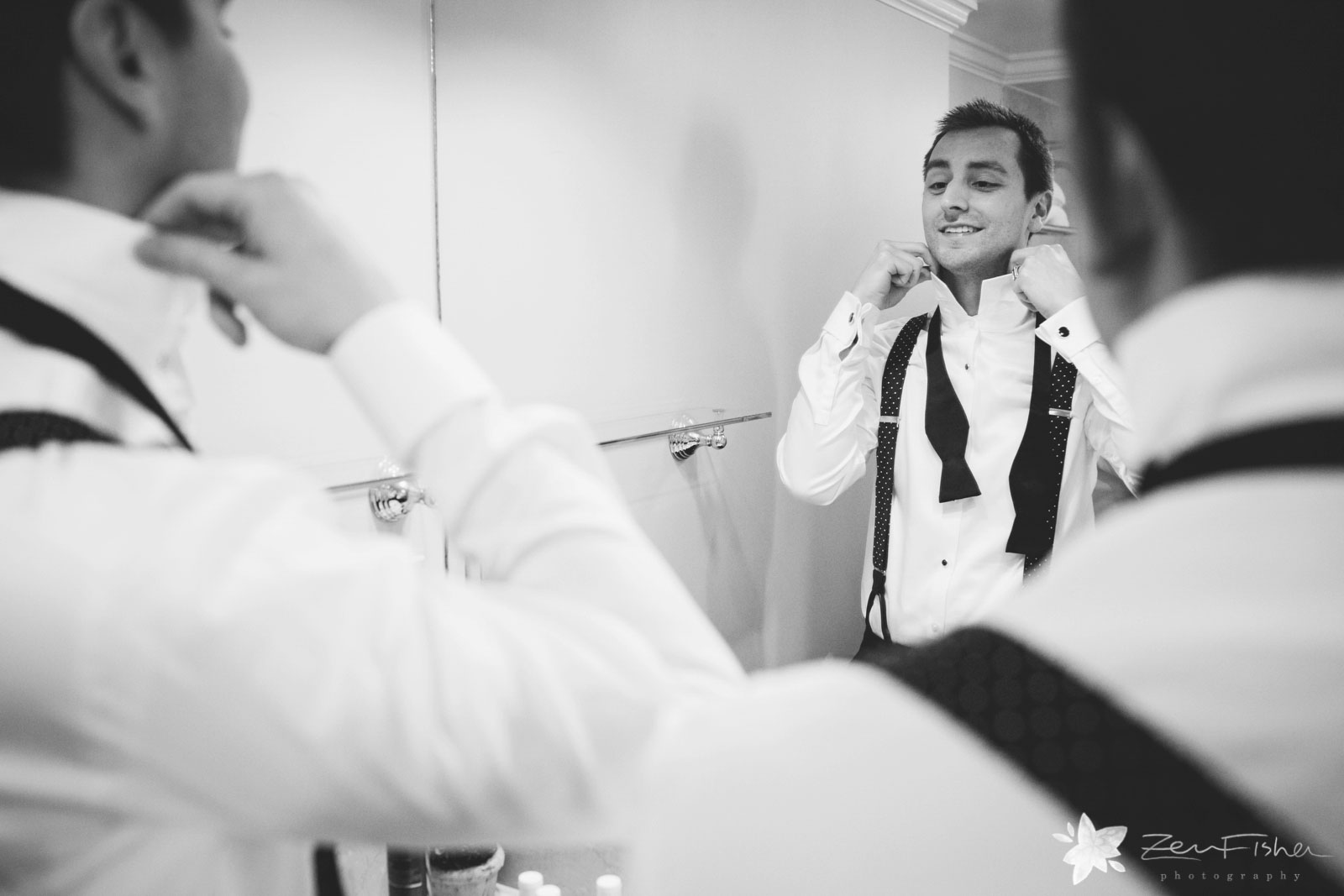 Groomsman getting ready in the hotel suite, looking in the mirror tying his bow tie.
