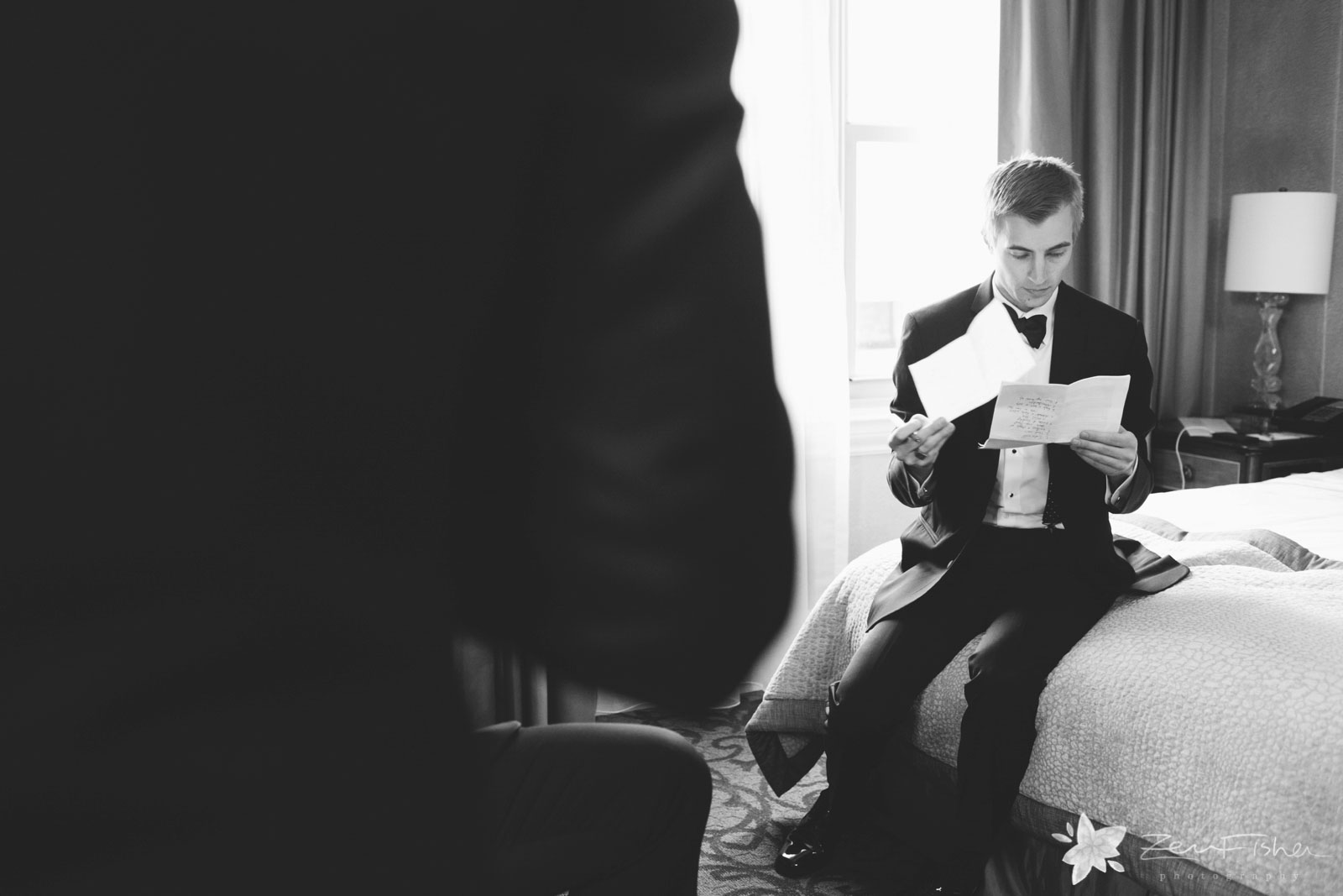 Groom sits on bed in hotel room and reads through his hand-written vows, making final touches.