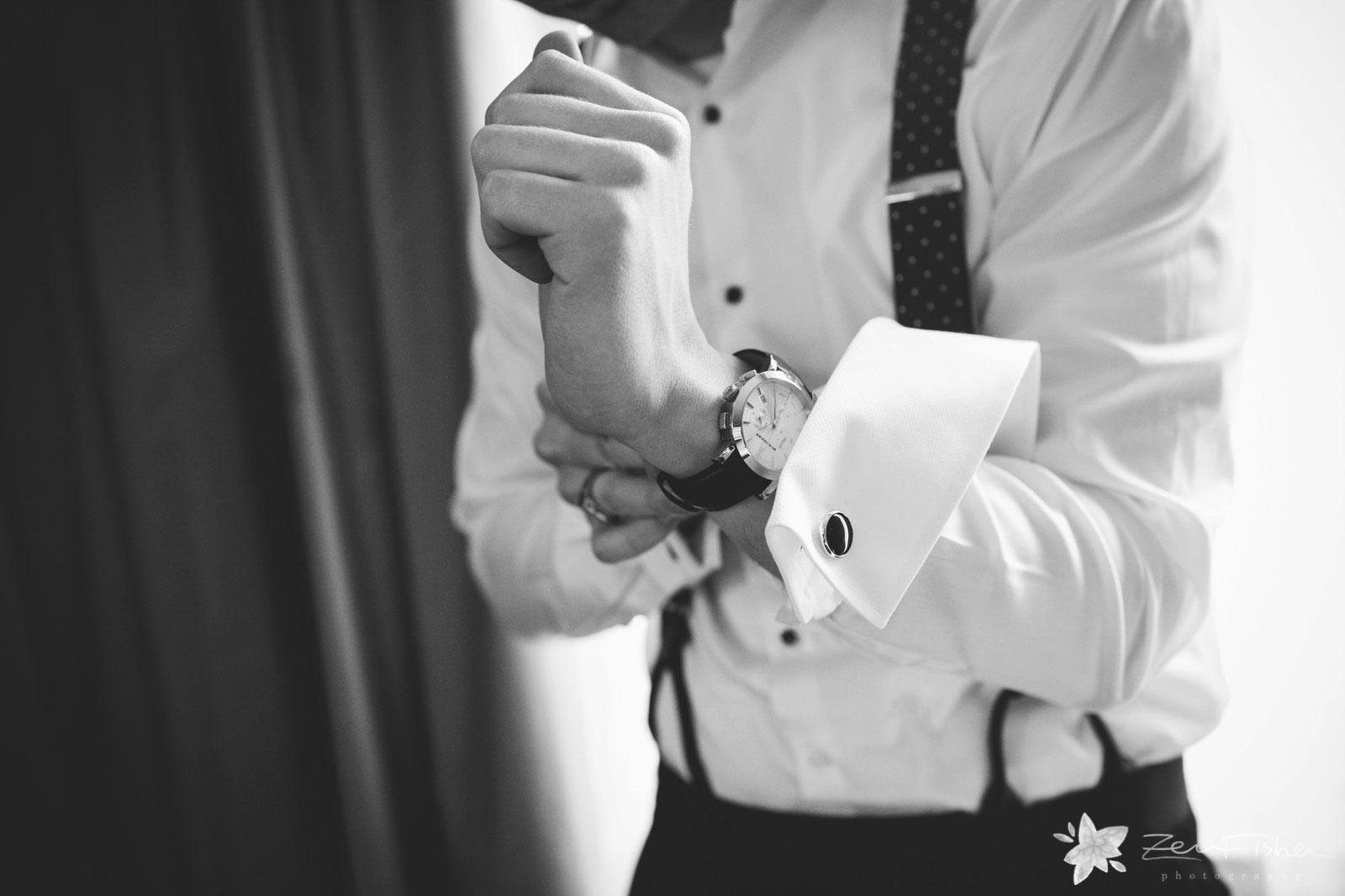 Close up of groom getting ready in hotel room, fastening his watch and putting his cuff links on.