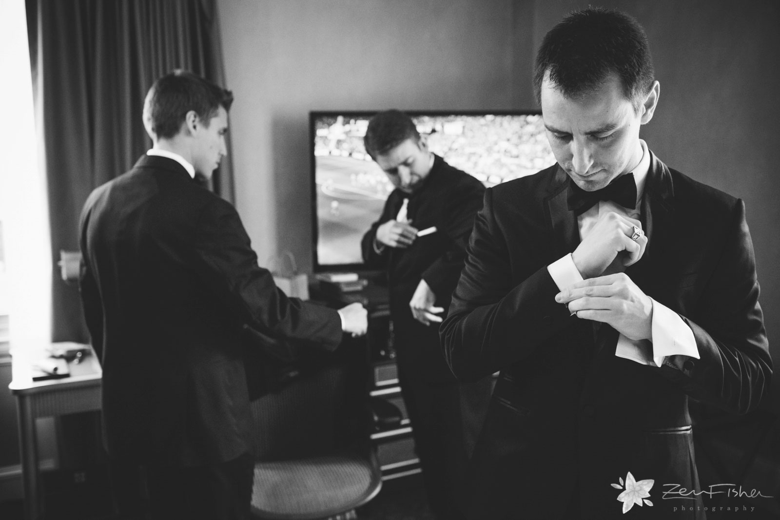 Groom and groomsmen at hotel putting final touches on their tuxes, pocket squares, and cuff links.