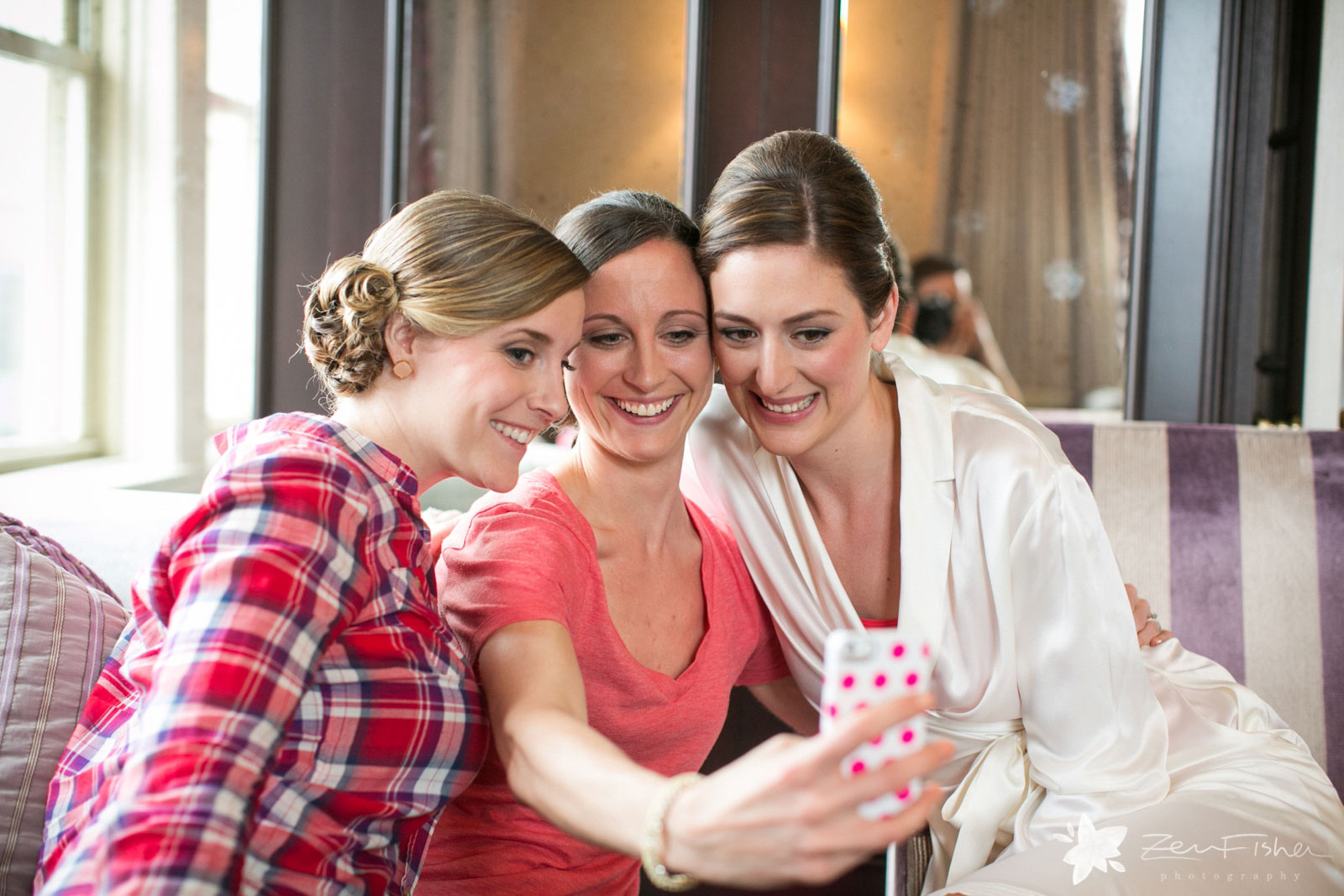 Bride and bridesmaids having fun getting ready in the hotel room taking a selfie and smiling.