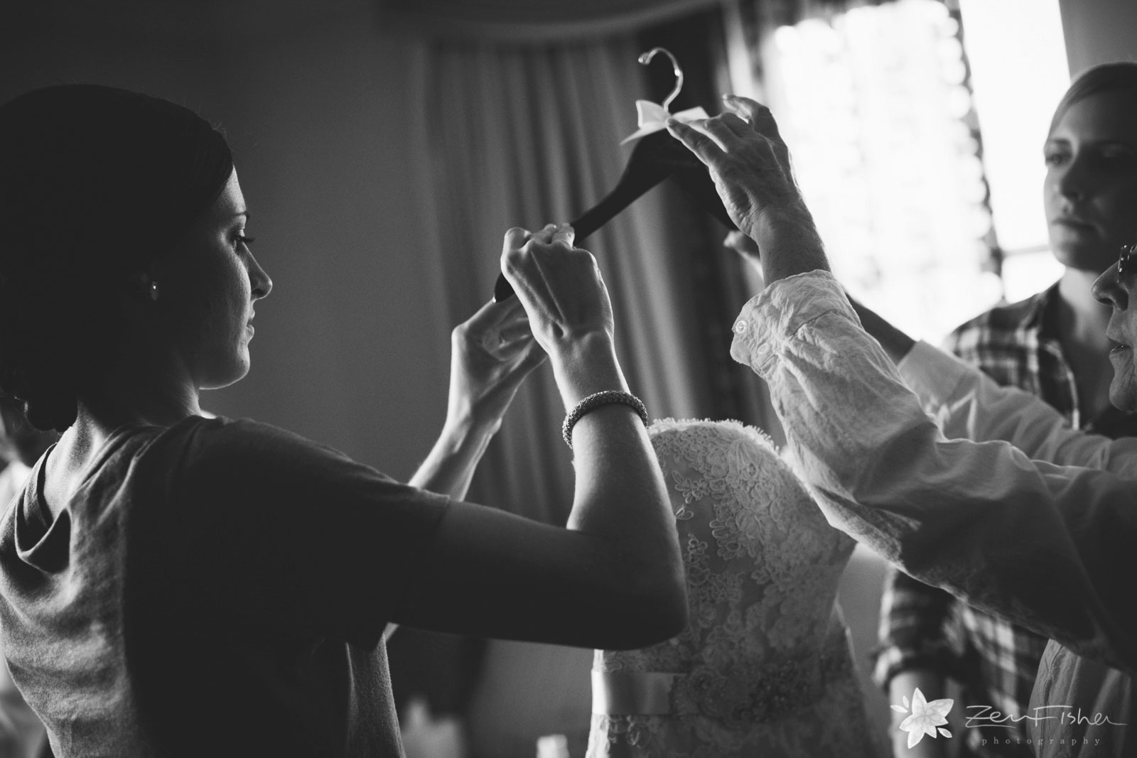 Bridesmaid and mother of the bride take wedding dress off the hanger, in dramatic black and white.