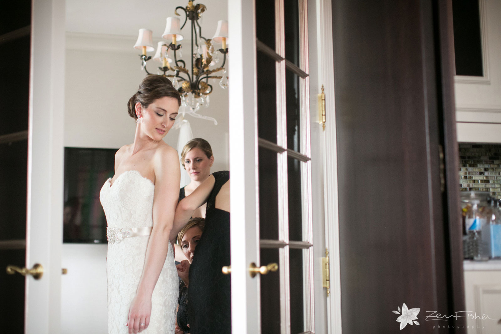 Peeking through French doors at the bride, bridesmaids helping the bride get into her wedding dress.