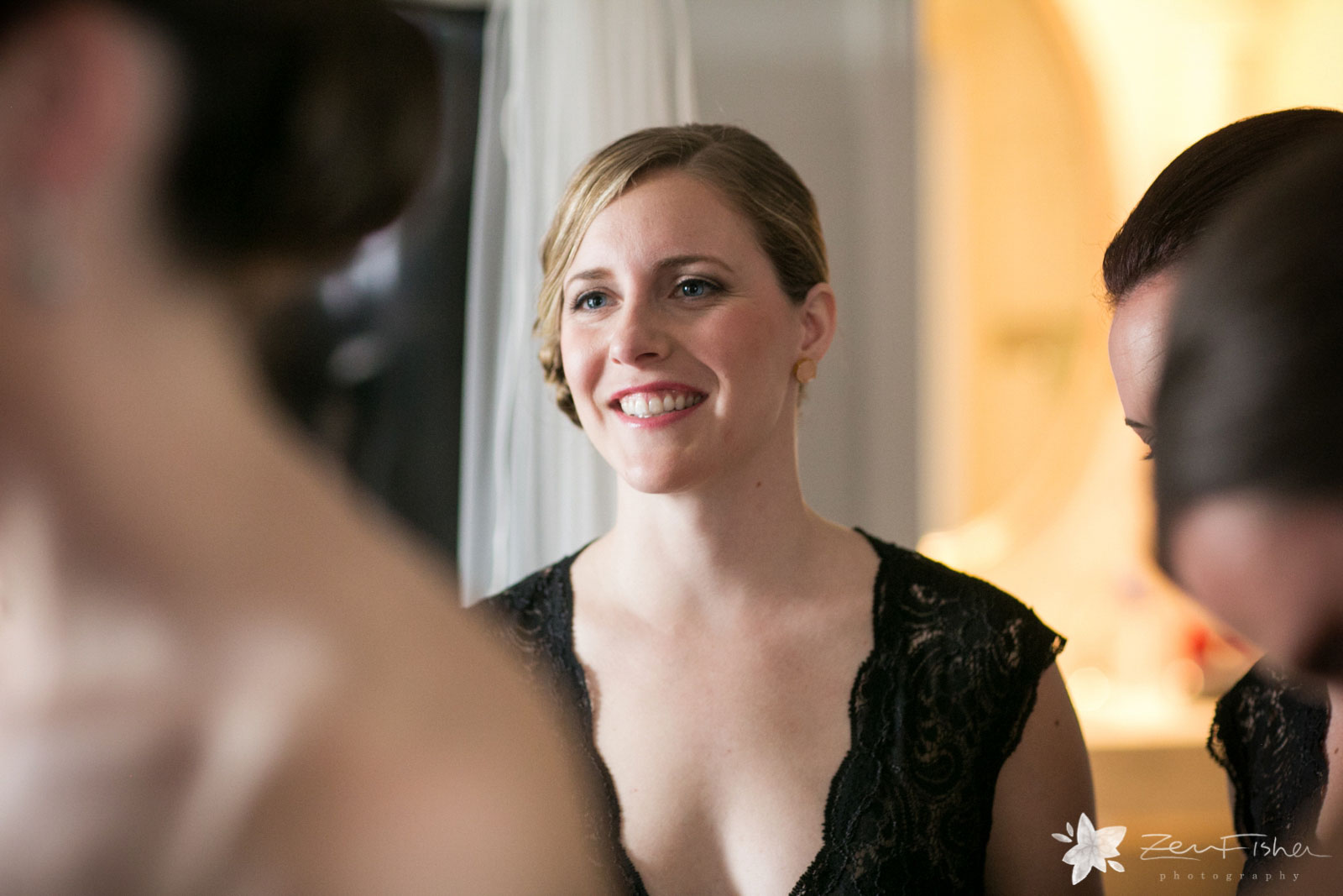 Candid of bridemaid looking at bride and smiling.