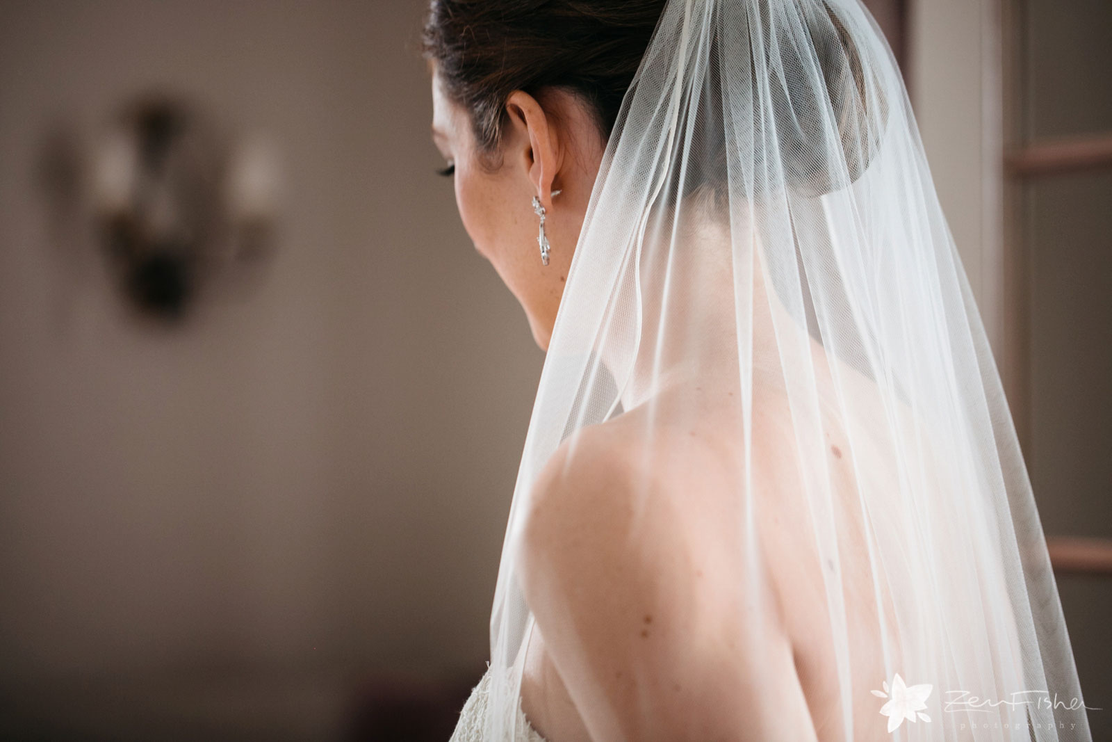 Detail of bride looking away and wearing long flowing veil and crystal earrings.