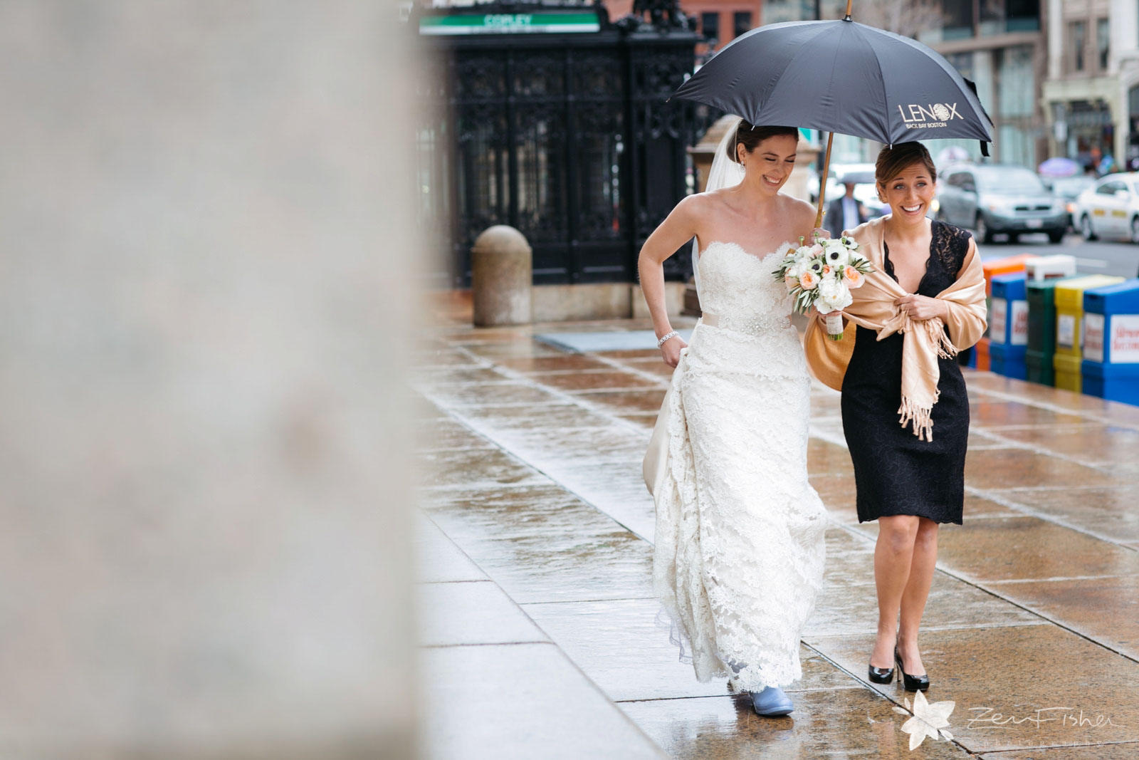 Peeking around the corner at bride and bridemaid walking down the street in the rain, laughing
