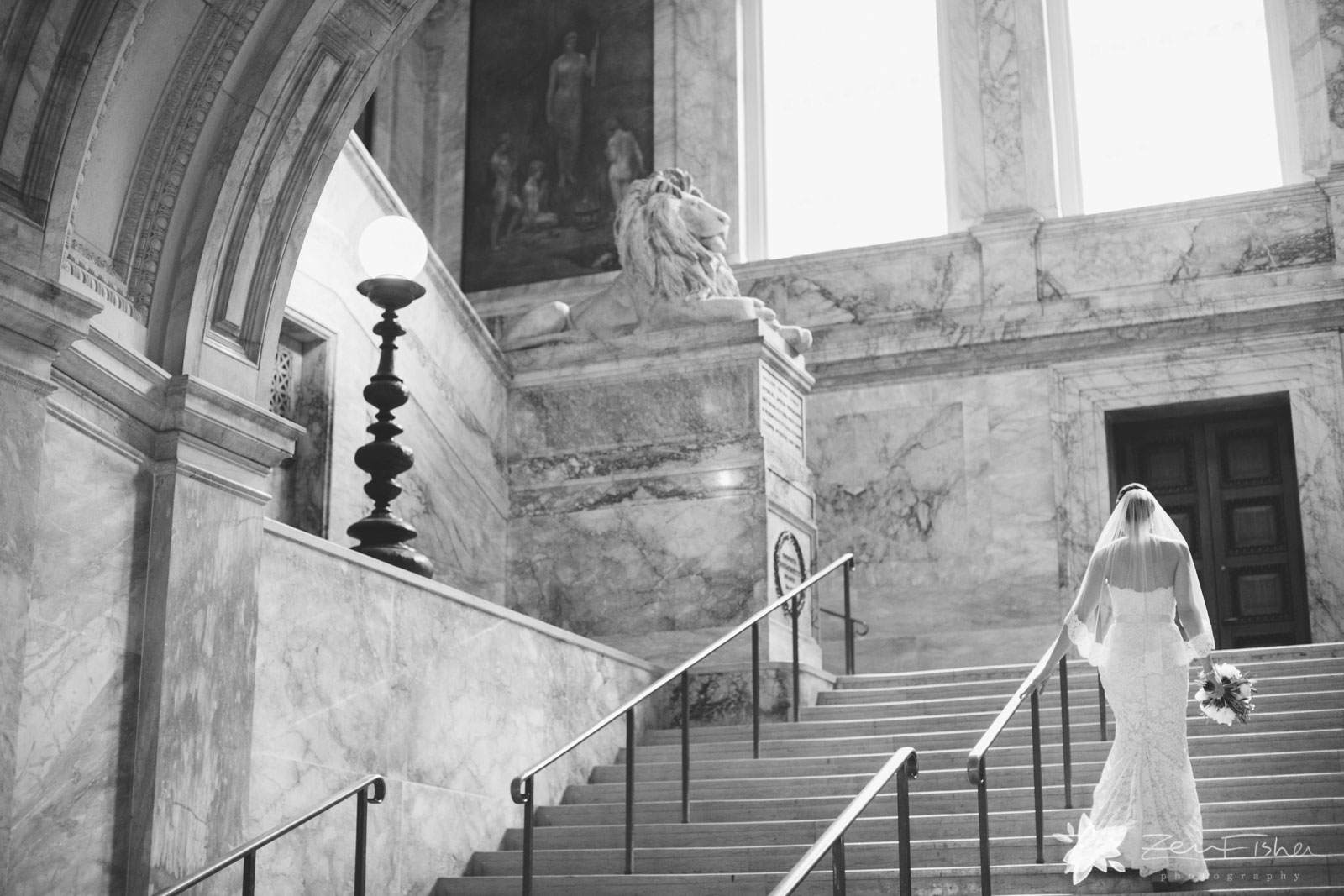 Bride from behind walking up the stairs at the elegant marble entrance to the Boston Public Library.